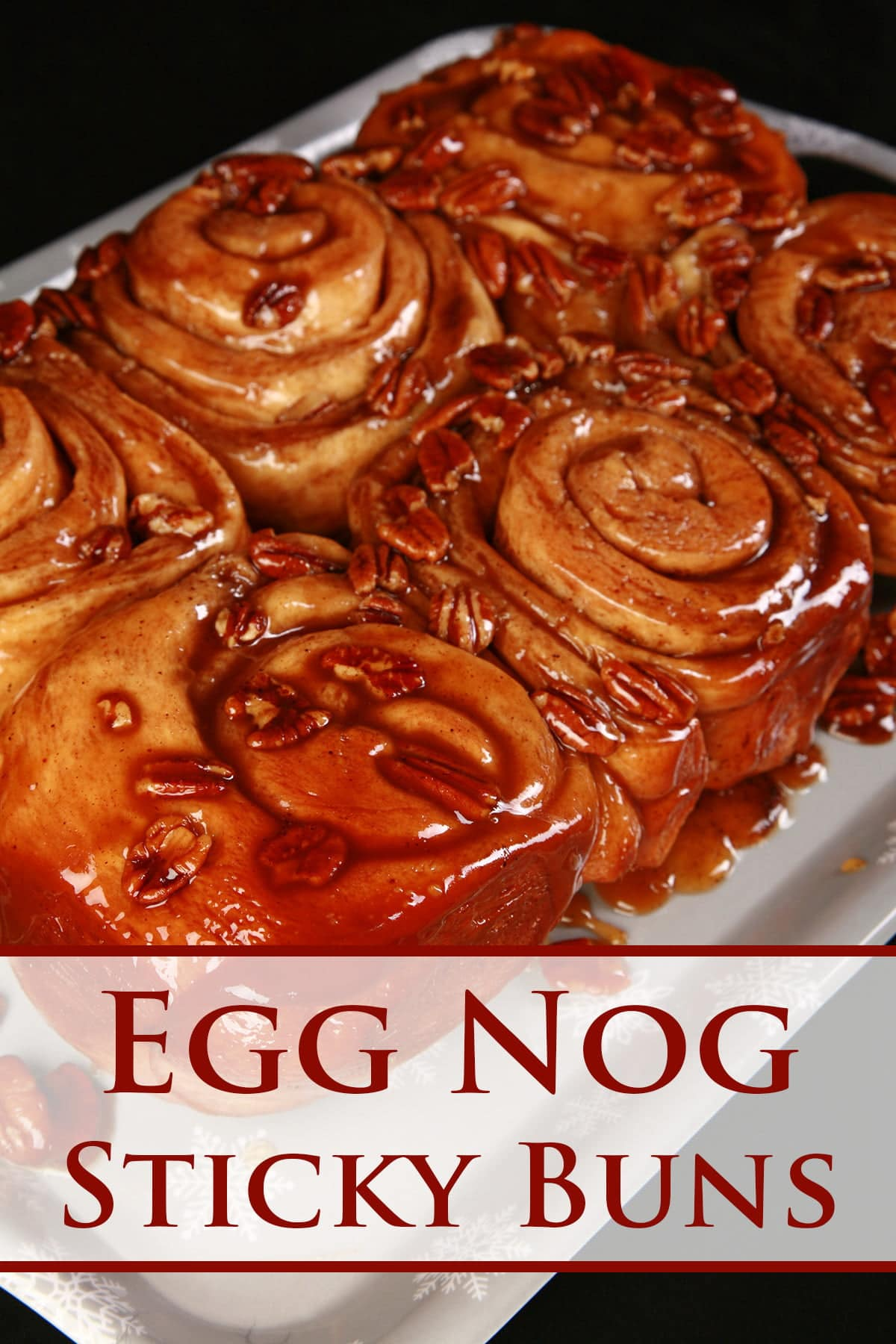 A close up view of a slab of 6 egg nog sticky buns. They are dripping with caramel and pecans.