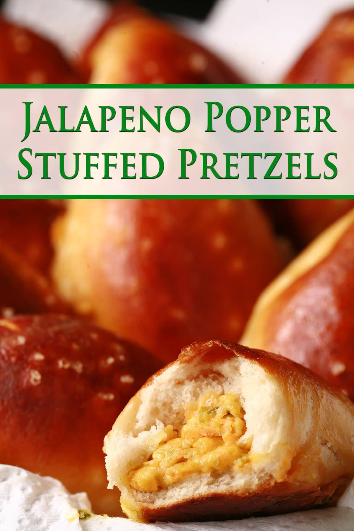 A napkin lined plastic food basket is full of golden brown jalapeno popper stuffed pretzels. In the foreground, one of the buns has a bite taken out, revealing a jalapeno and cheese filling.