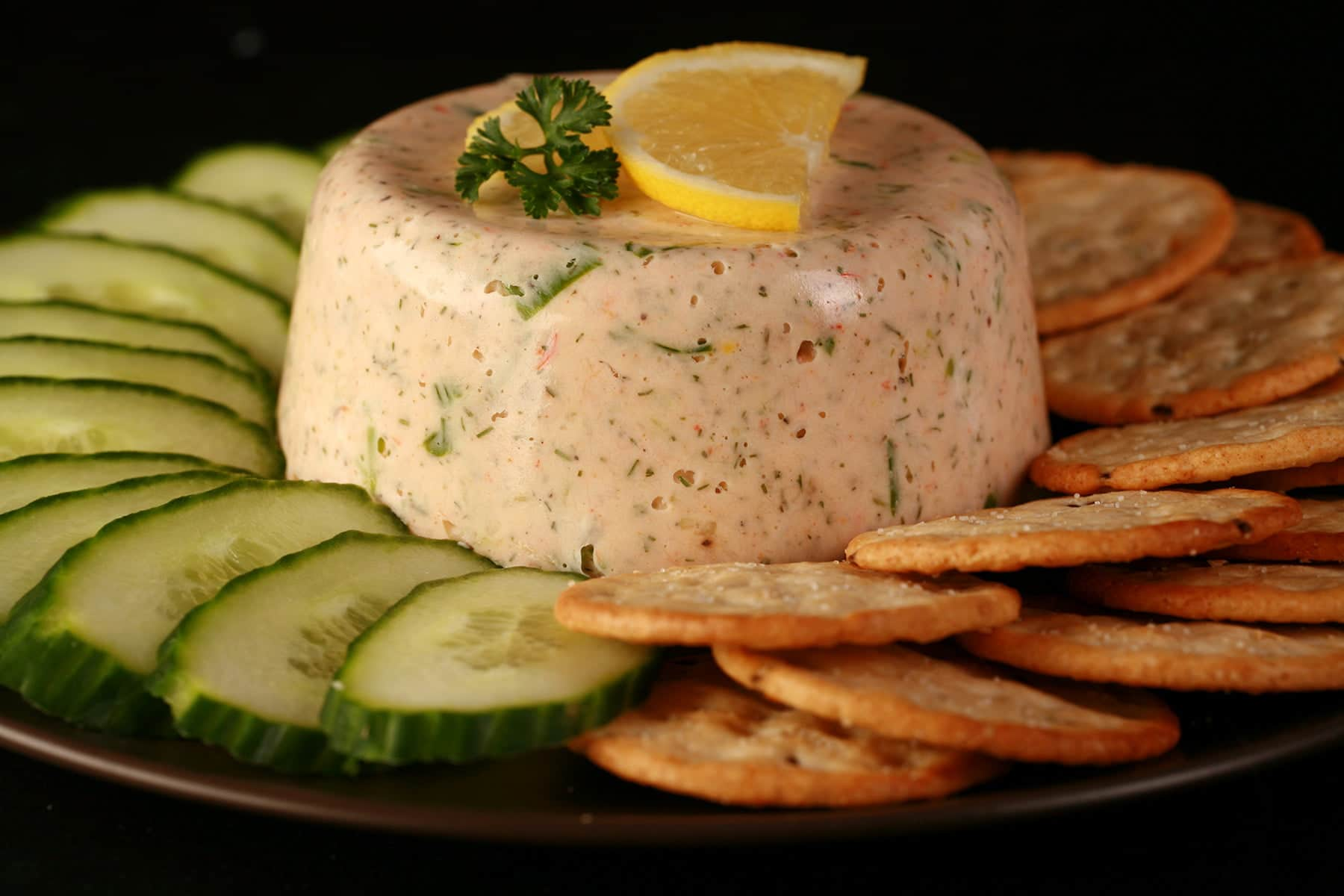 A closeup view of shrimp mousse. It is topped with slices of lemon and a sprig of parsley, and is surrounded by cucumber slices and crackers.