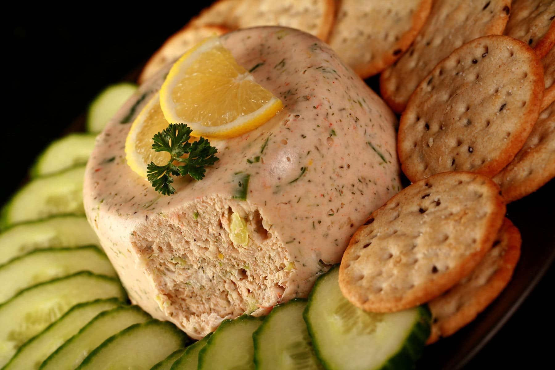 A closeup view of crab mousse. It is topped with slices of lemon and a sprig of parsley, and is surrounded by cucumber slices and crackers.