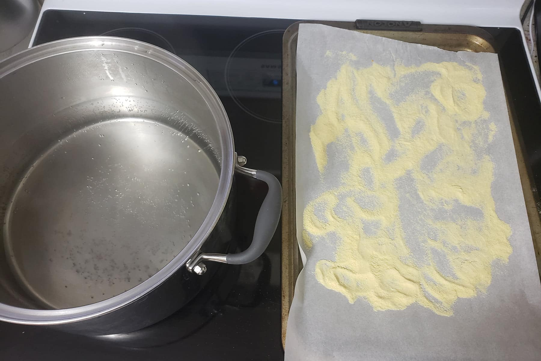 A large pot of water next to a parchment lined baking sheet. The parchment has cornmeal scattered over it.
