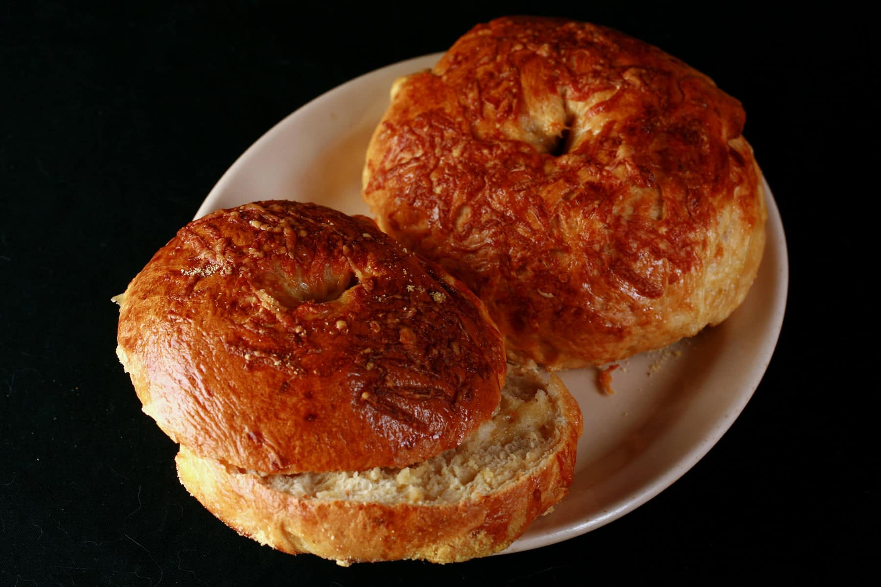 Two cheese covered bagels on an oval plate. The bagel in the foreground has been sliced in half.