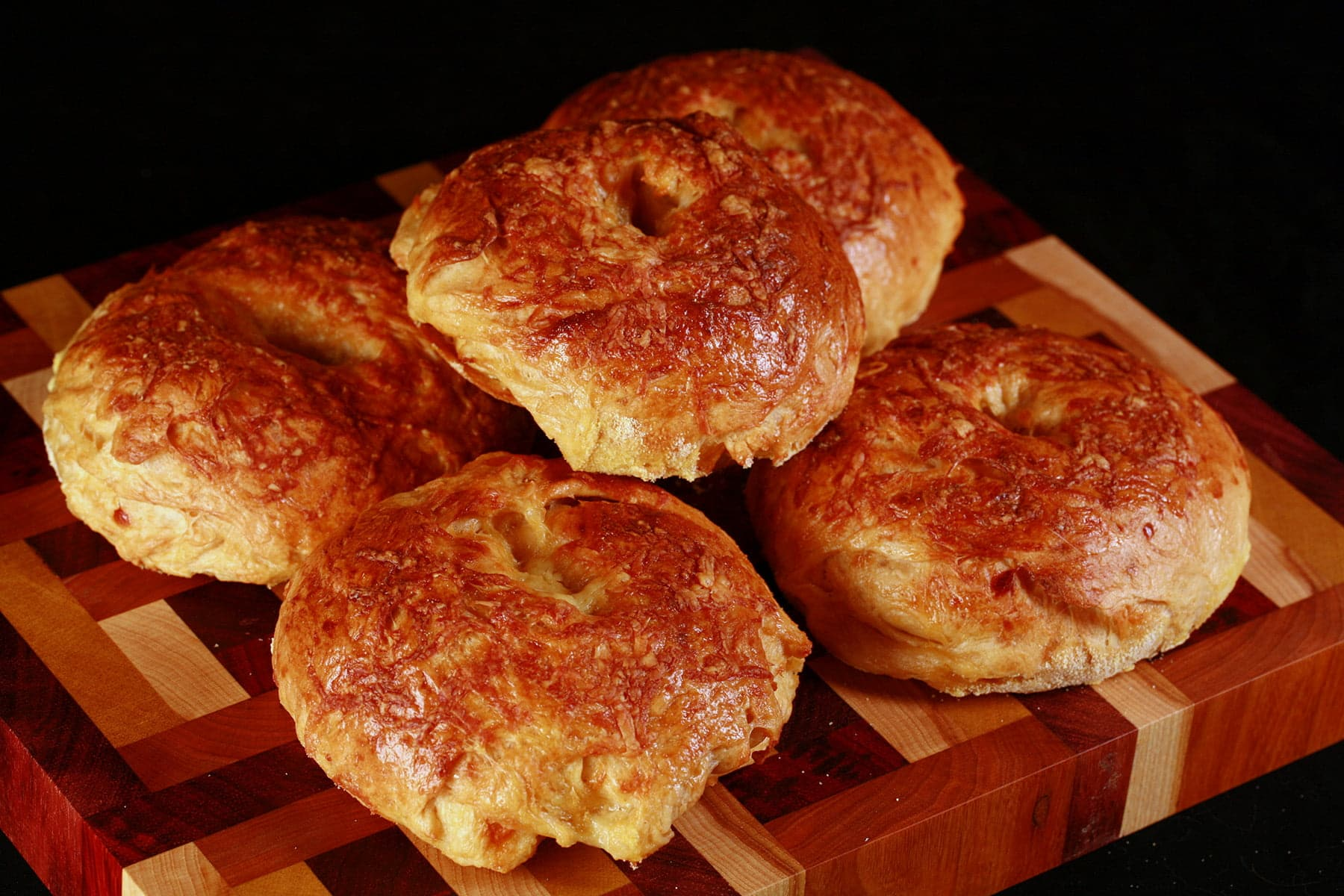 A pile of smoky cheese bagels on a multicoloured cutting board.
