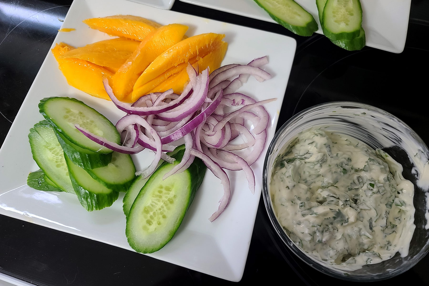 Slices of mango, cucumber, and red onion on a white plate, next to a small glass bowl of cilanto-mint mayonnaise.