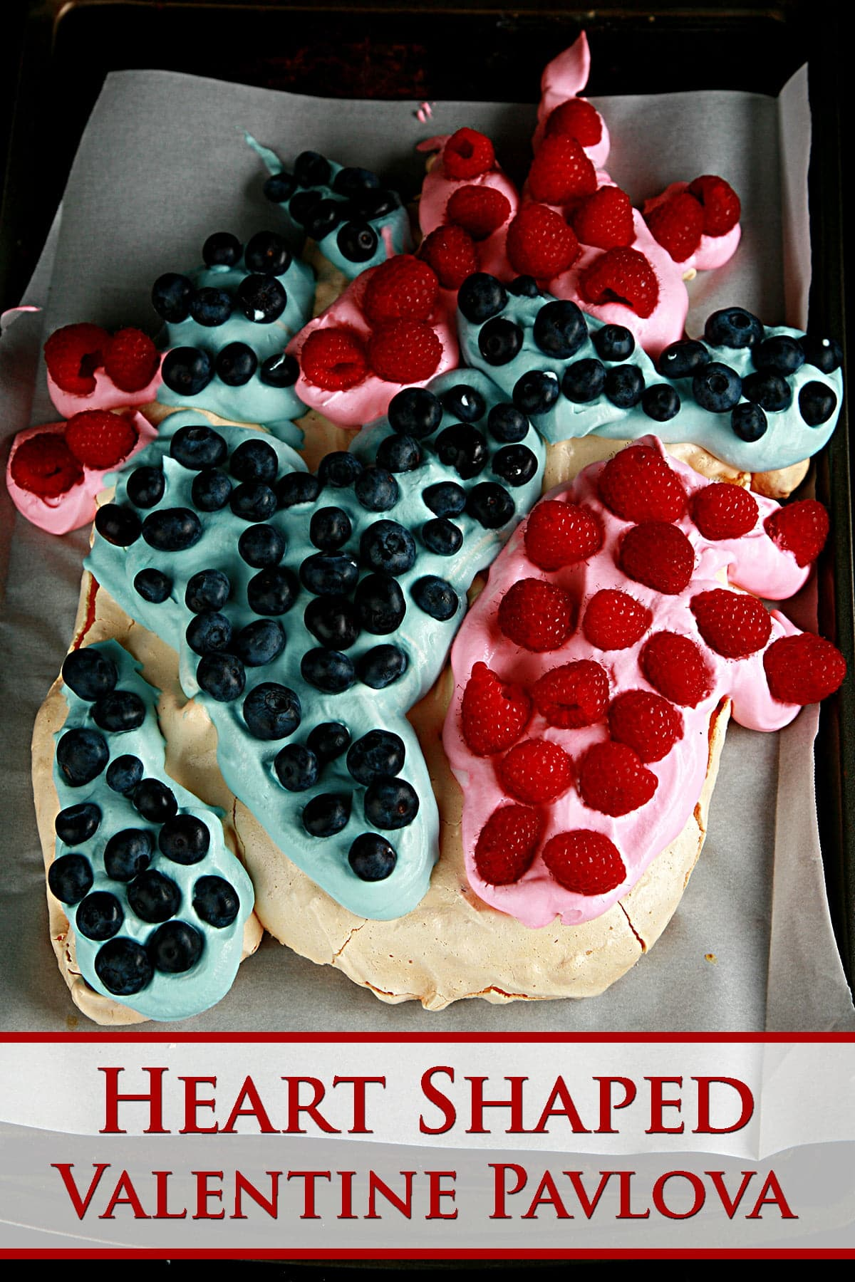 A heart shaped pavlova, with blue and red whipped cream, raspberries, and blueberries.
