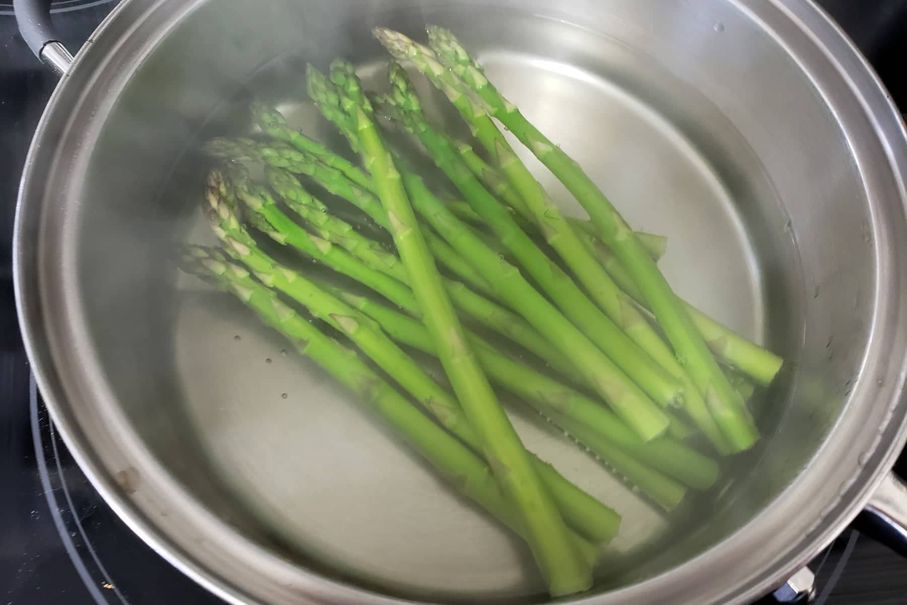 About a dozen spears of asparagus are shown simmering in a metal pan.
