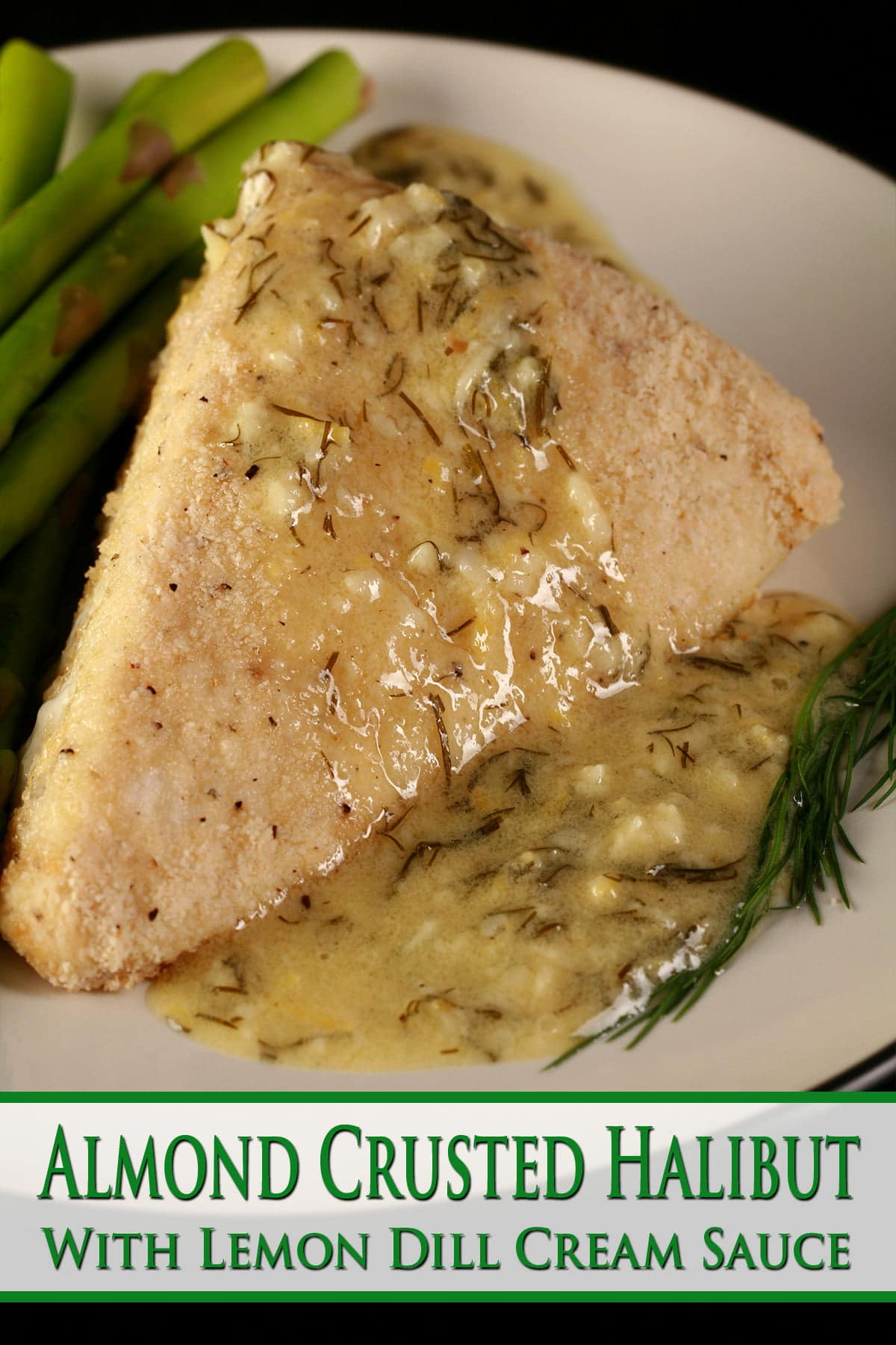 A large piece of almond crusted halibut is on a white plate. A yellow cream sauce with flecks of green - lemon dill cream sauce - has been poured over the fish, and there are asparagus spears on the side.