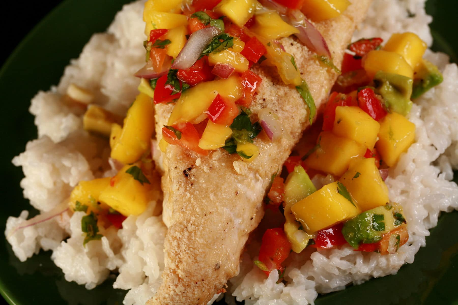 A generous portion of cashew crusted halibut steak is shown on top of a bed of coconut rice. It is topped with brightly coloured mango salsa.