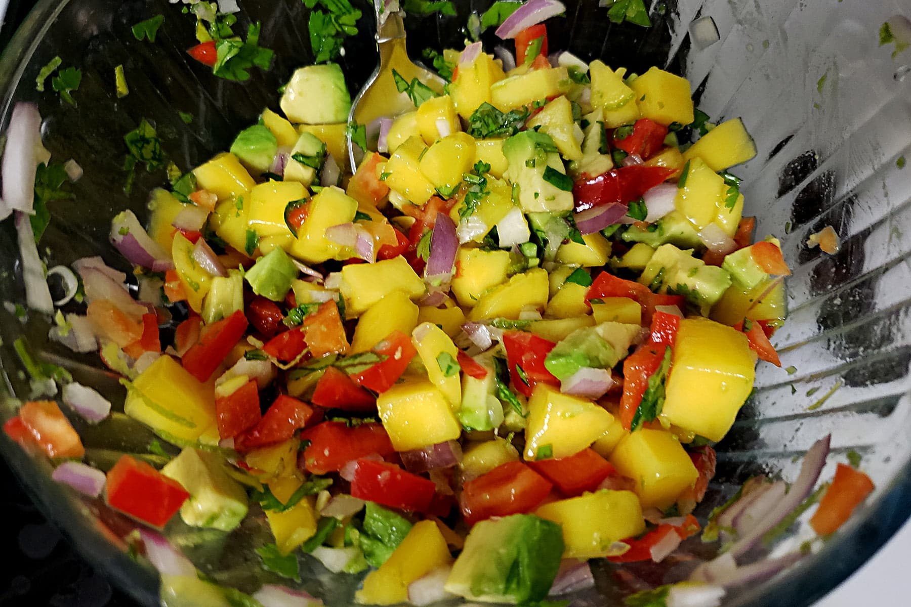 A close up view of a glass bowl of mango salsa. Mango, red pepper, avocado, red onion, and chopped cilantro is shown.