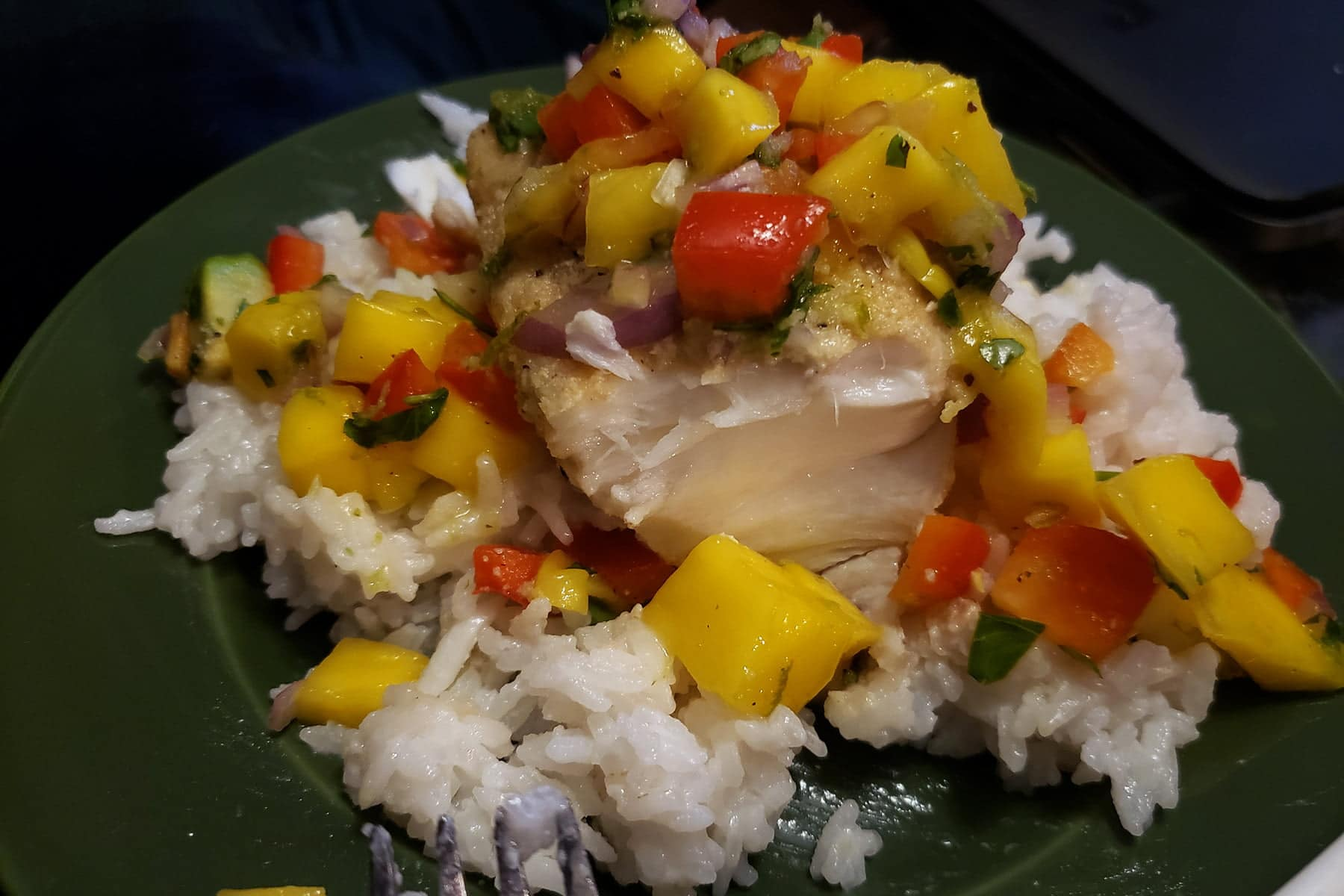 A cell phone photo of a serving of cashew crusted halibut with mango salsa on top. Part of the fish has been flaked away, showing the meaty white interior.