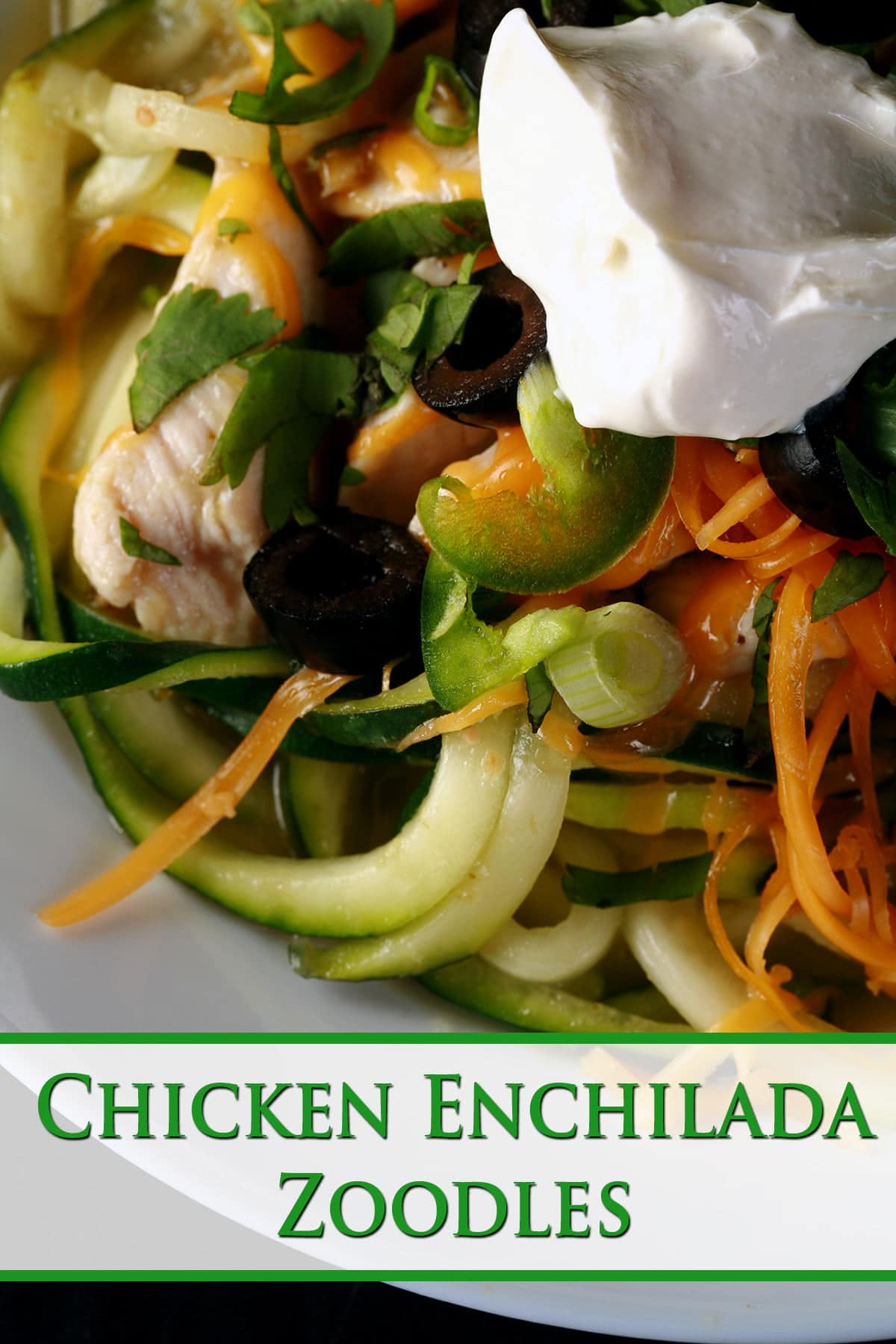 A close up view of chicken enchilada zoodles - a low carb, gluten-free meal of sauteed chicken and zuchinni noodles in salsa verde, topped with cheese, green onions, cilantro, black olives, and sour cream.