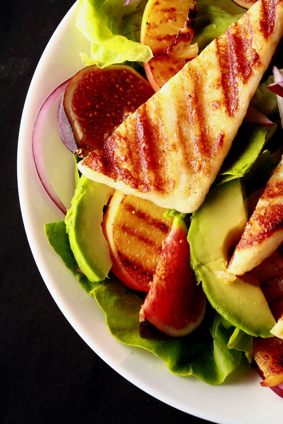 A bowl of salad, with sliced figs, grilled peaches, and strips of grilled white cheese. Grilled Halloumi Salad with Peaches and Figs