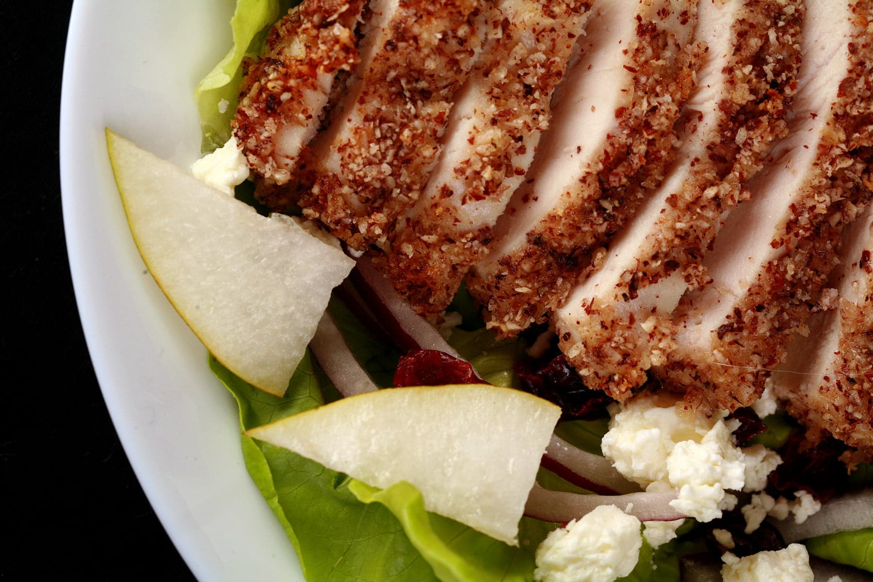 A sliced hazelnut crusted chicken breast sits a top a salad of greens, pear slices, dried cranberries, red onion slices, and feta.