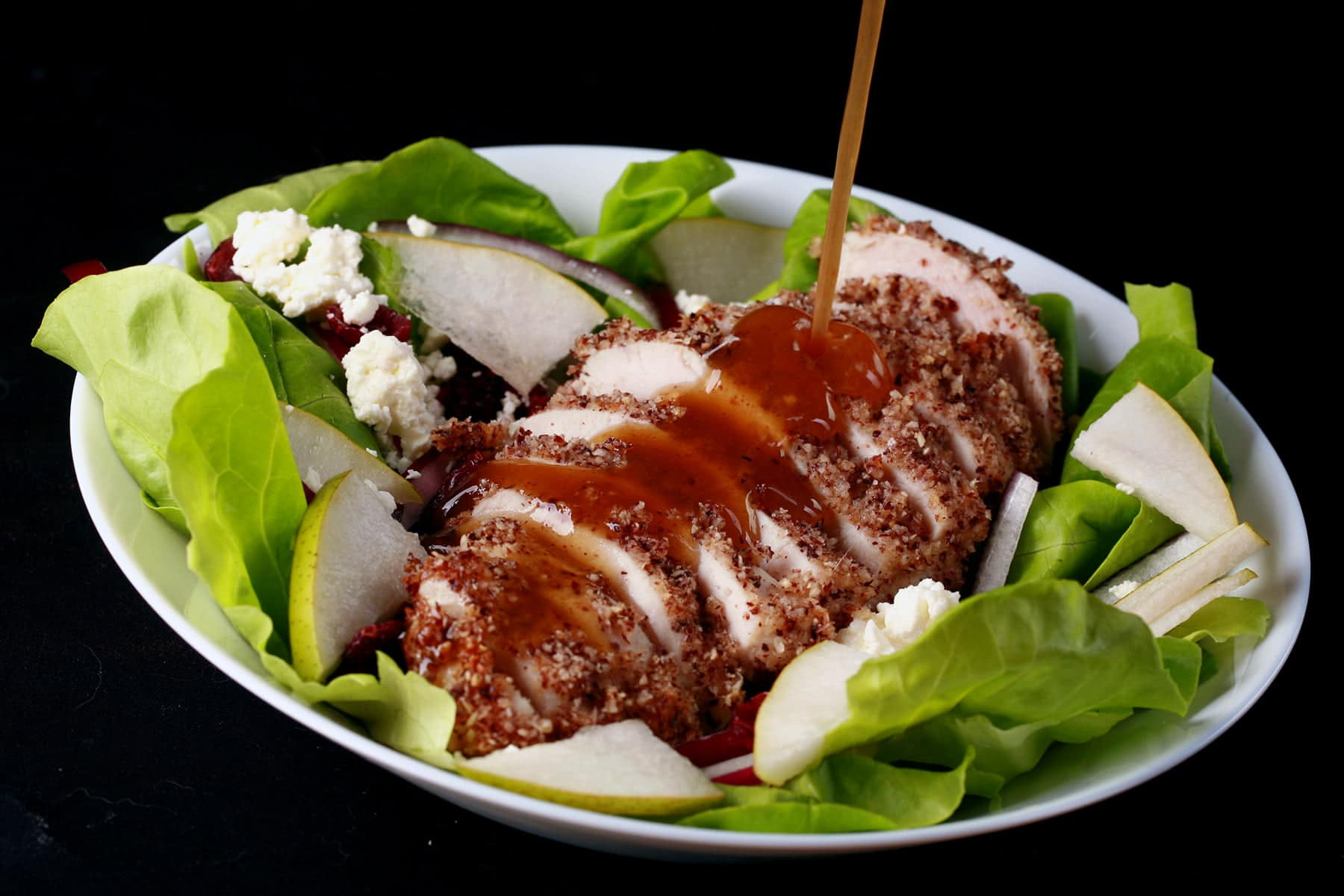 A sliced hazelnut crusted chicken breast sits a top a salad of greens, pear slices, dried cranberries, red onion slices, and feta. A golden brown balsamic vinaigrette is being poured across the chicken.