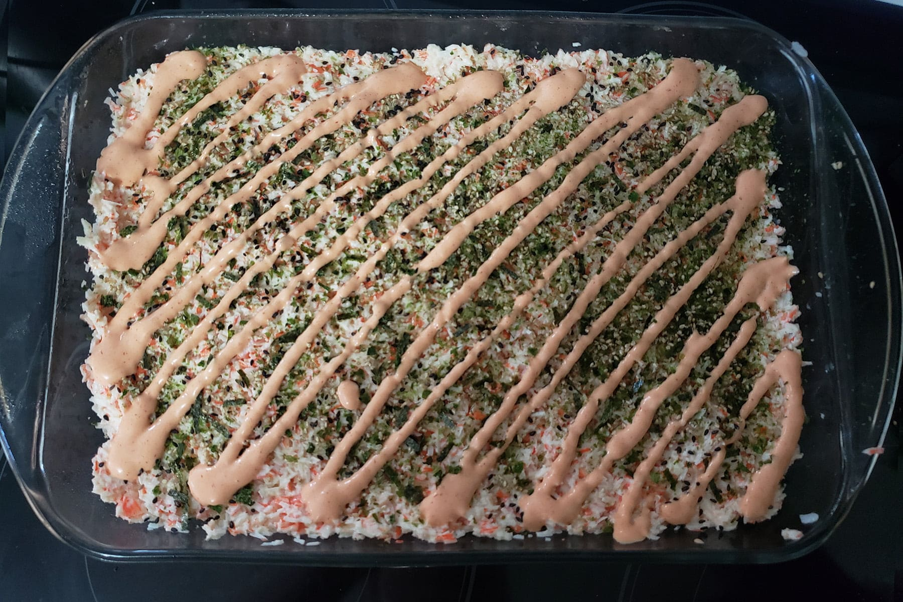 The unbaked sushi casserole is shown with a pink drizzle of spicy mayo all over it, in diagonal lines.