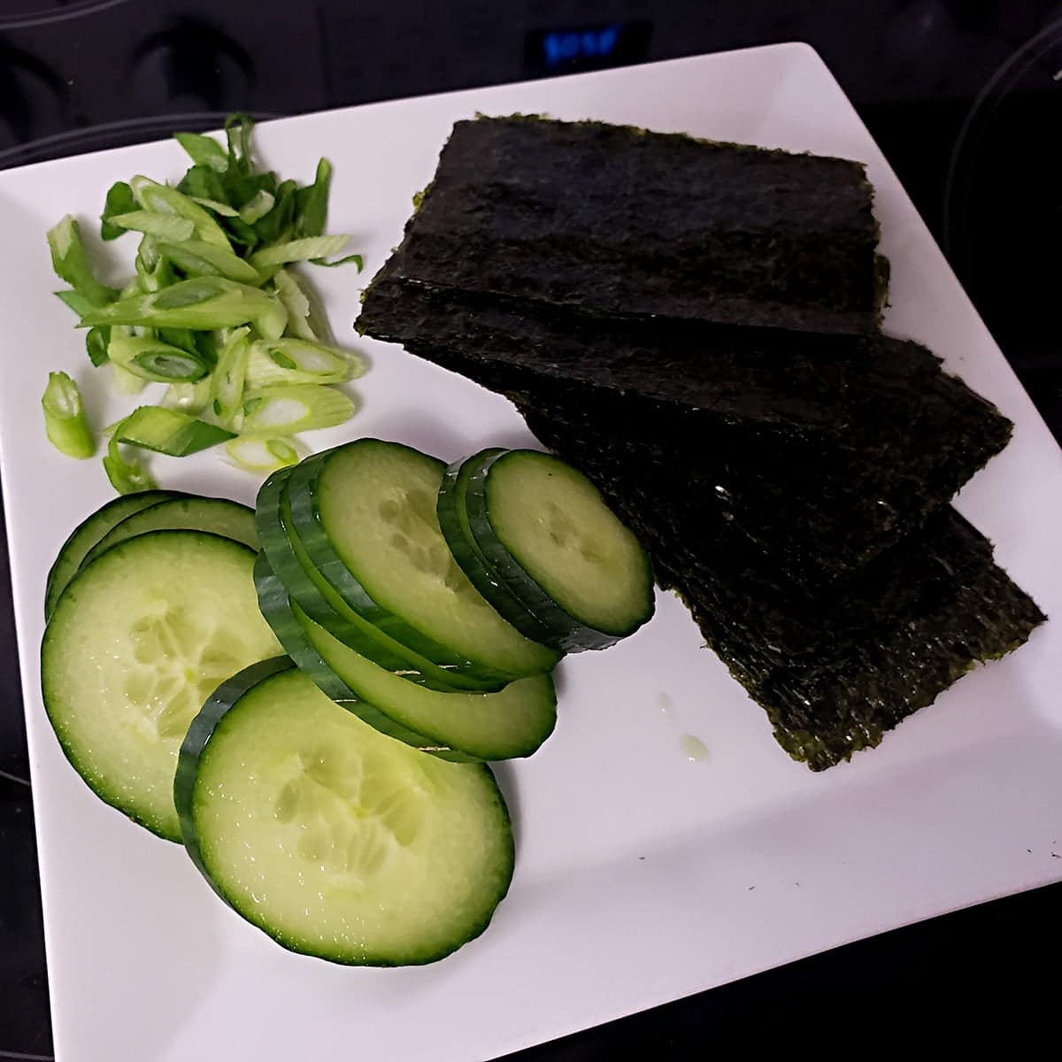 A white cutting board with slices of cucumber and green onions on it, along with pieces of nori - seaweed sheets.