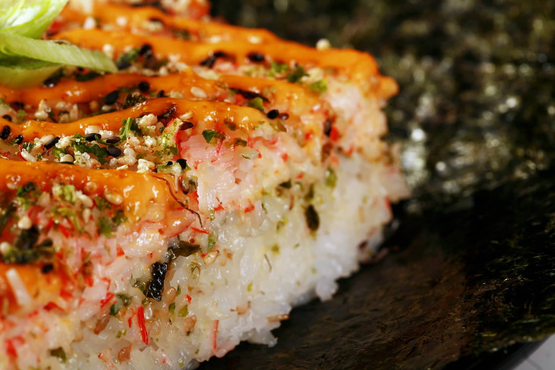 A close up view of a square serving of sushi bake - A casserole made from sushi rice, furikake, and a spicy imitation crab topping.