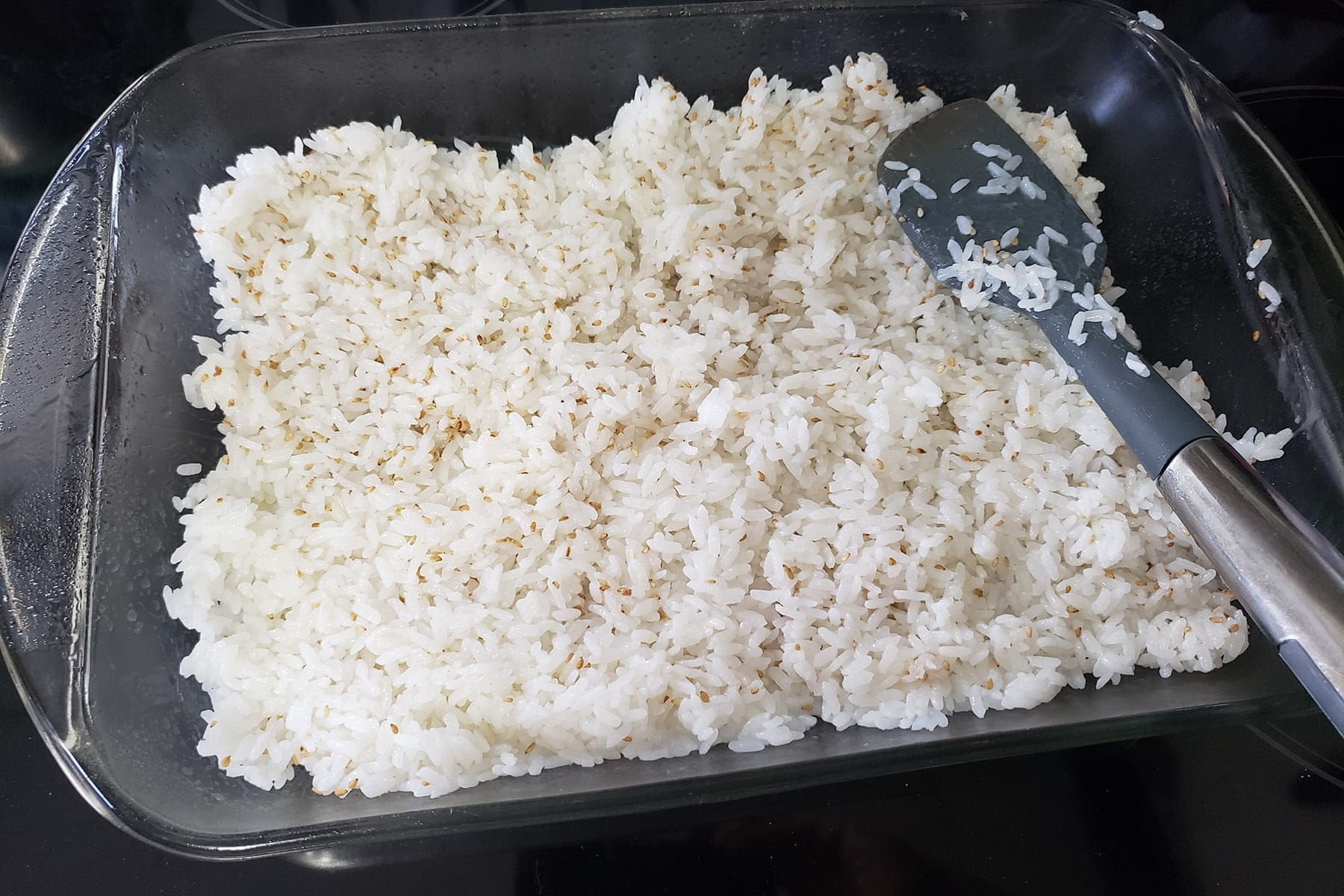 Sushi rice is being spread in a greased casserole dish.