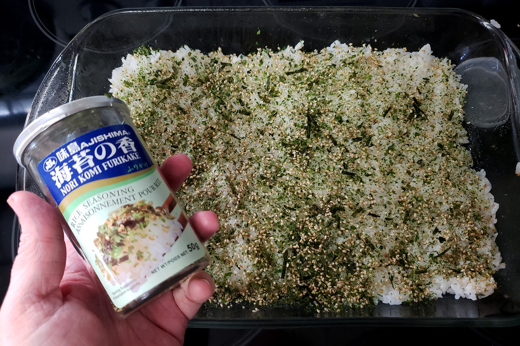 A hand holds a canister of furikake. The casserole dish with sushi rice in it is visible in the background, and has been generously sprinkled with the furikake.
