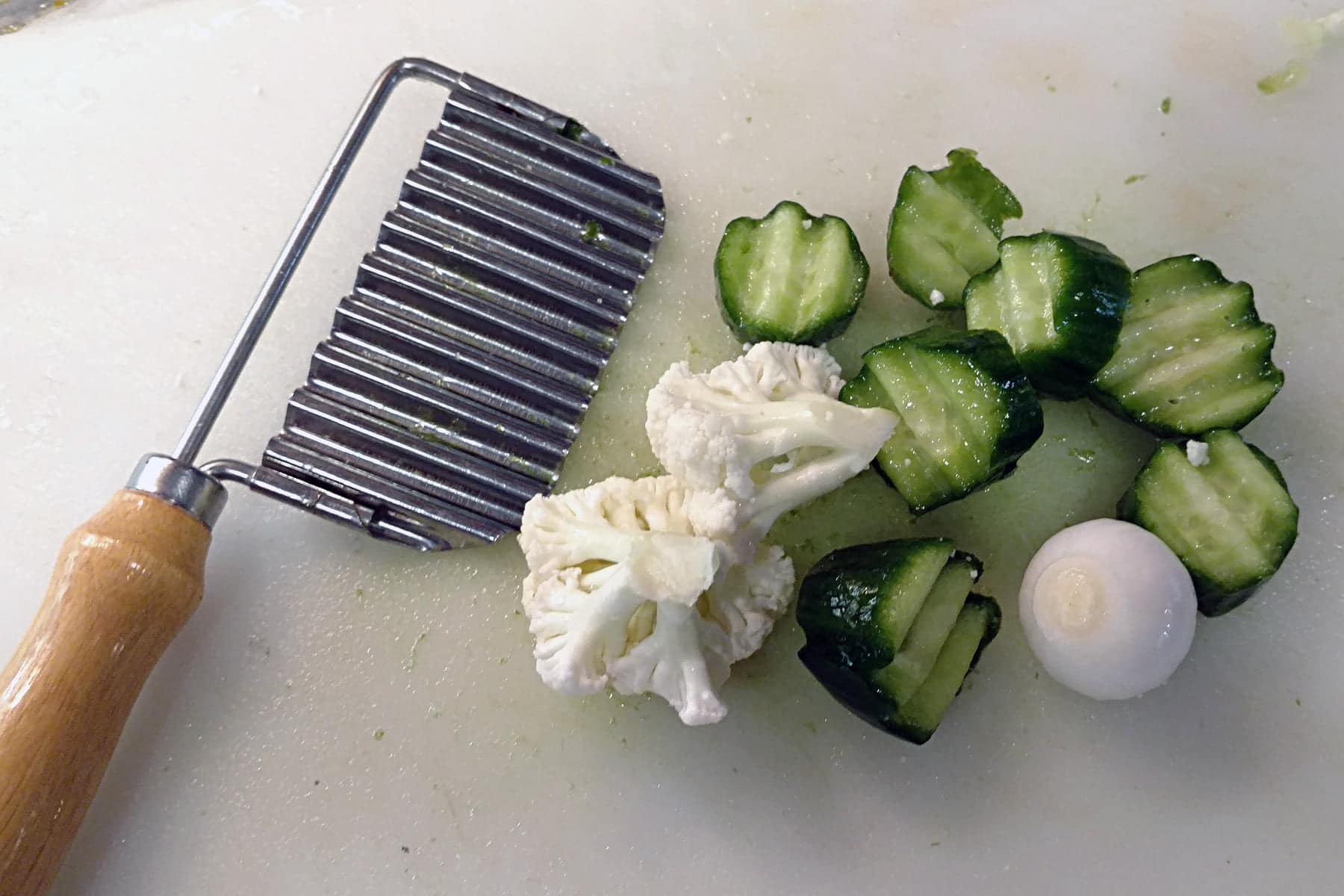 Cauliflower, wavy sliced cucumbers, and a wavy cutter, on a cutting board.