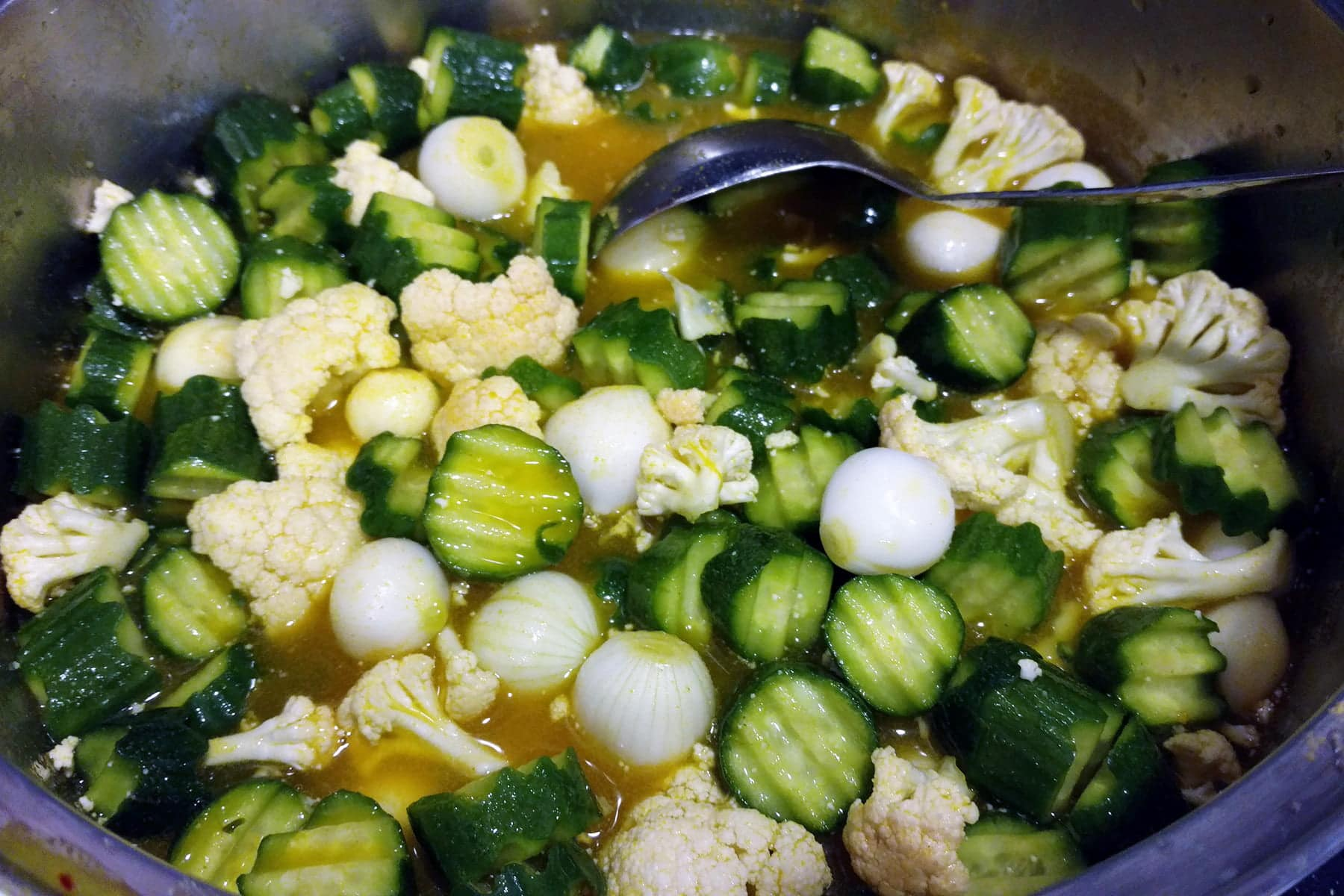 Wavy sliced cucumber, pieces of cauliflower, and pearl onions in a large pot, along with a yellow sauce.