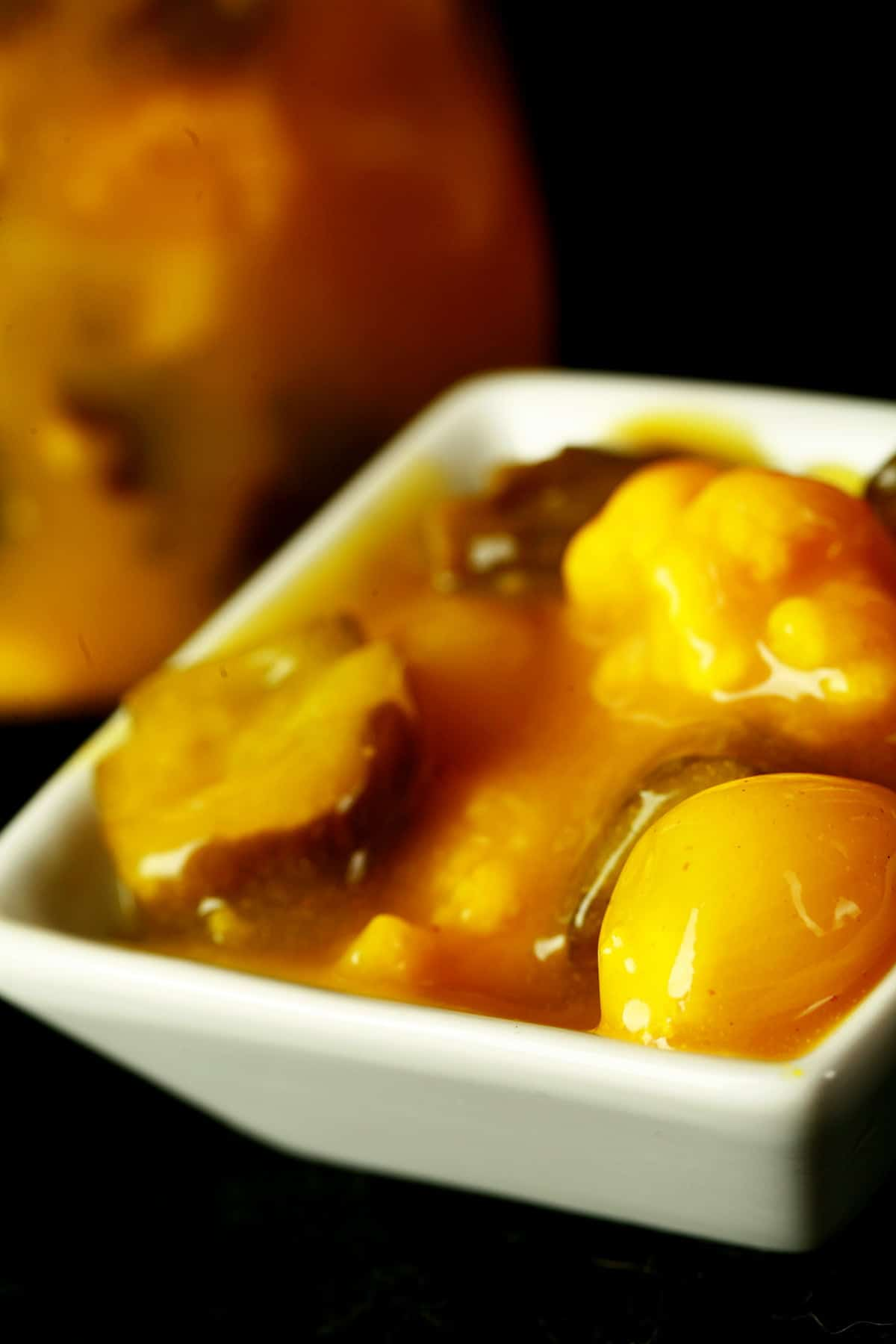 A small bowl of bright yellow sweet mustard pickles, in a thick sauce.