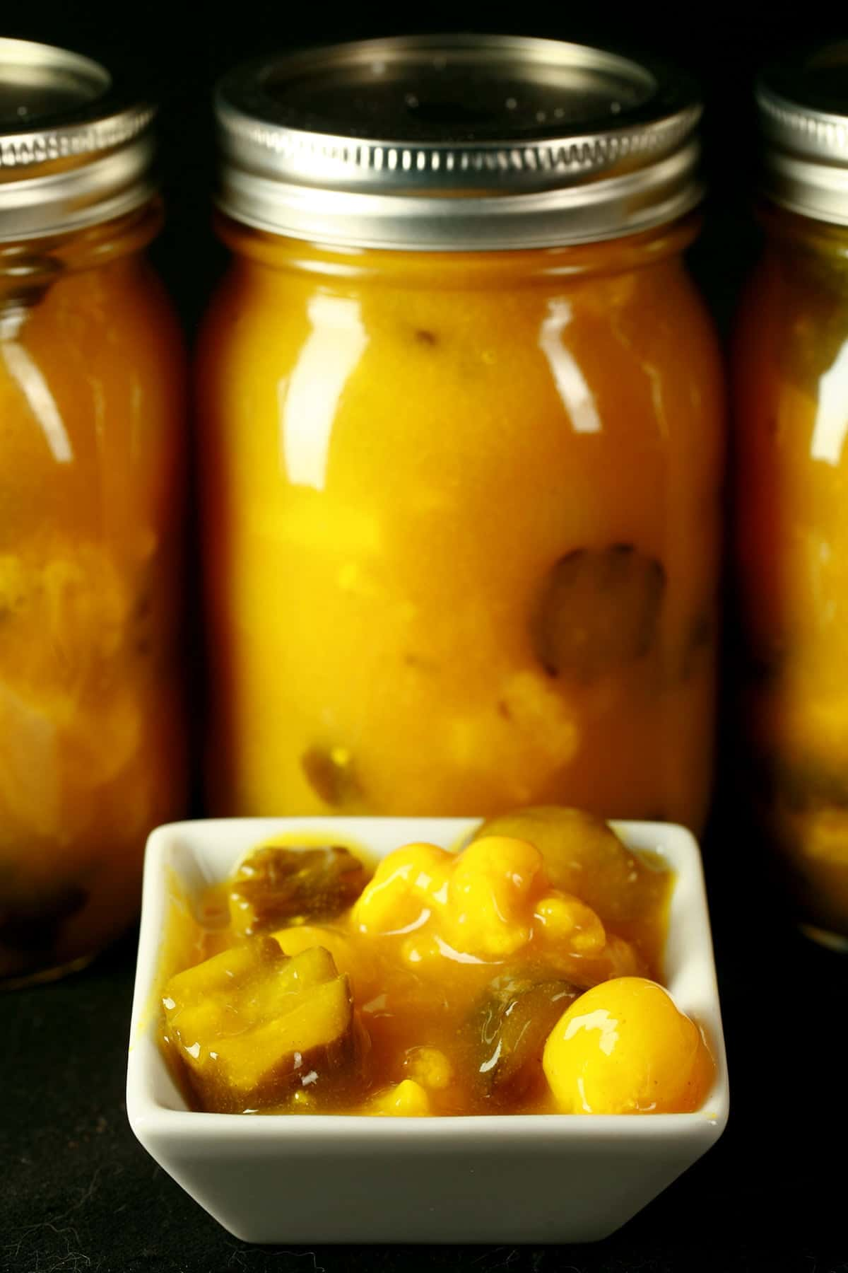 3 jars of bright yellow pickles, lined up behind a small bowl of mixed sweet mustard pickles.