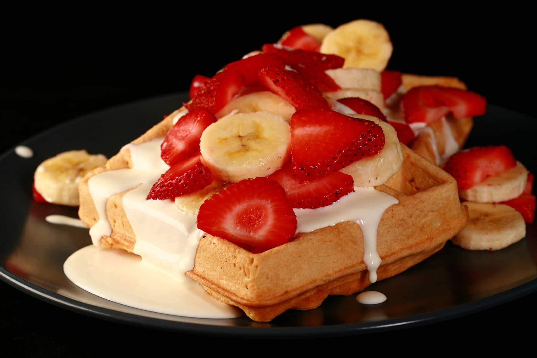 2 Ambrosia Waffles - Belgian waffles with cream cheese sauce, topped with sliced strawberries and sliced bananas - on a blue plate.