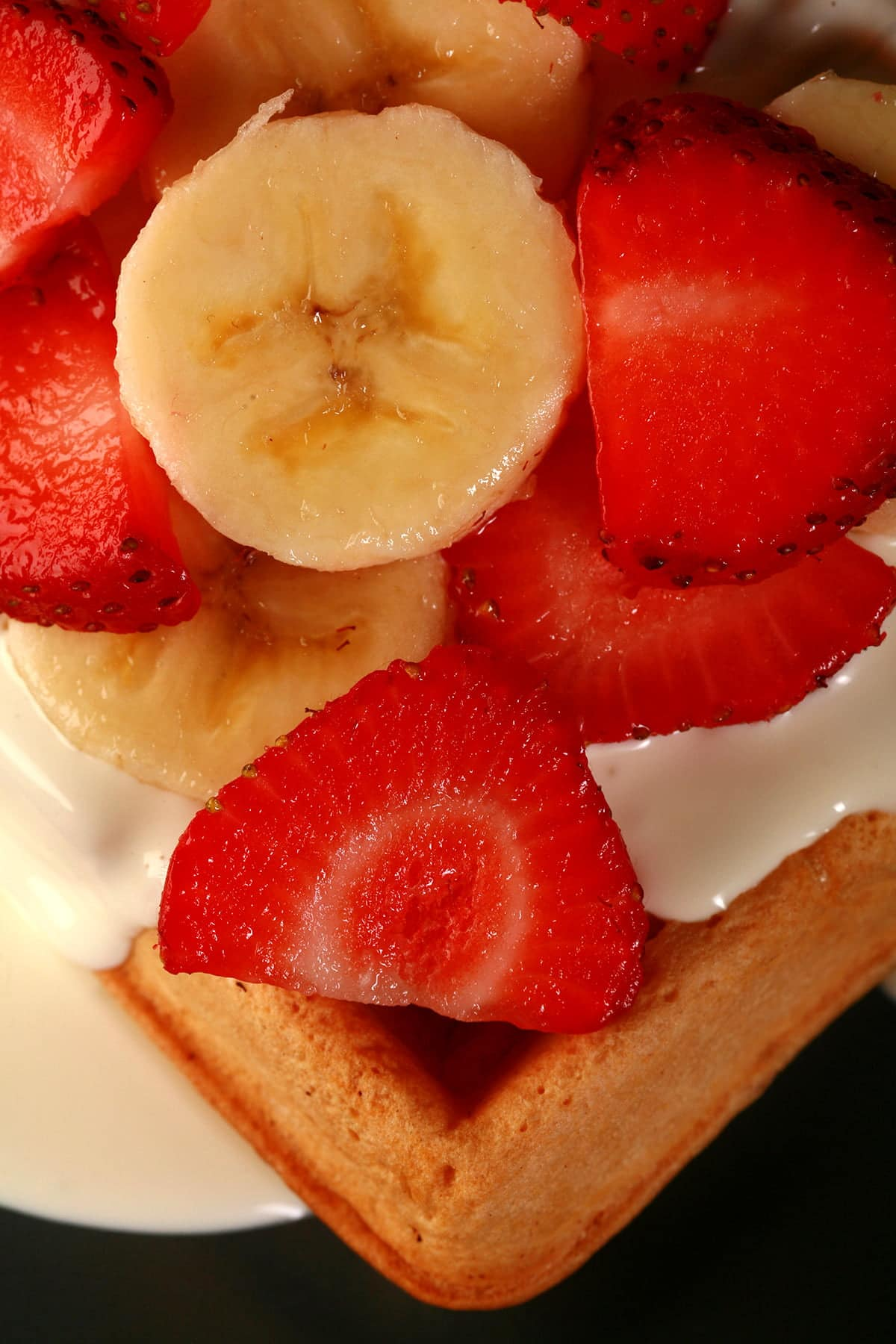 2 Ambrosia Belgian waffles - Belgian waffles with cream cheese sauce, topped with sliced strawberries and sliced bananas - on a blue plate.
