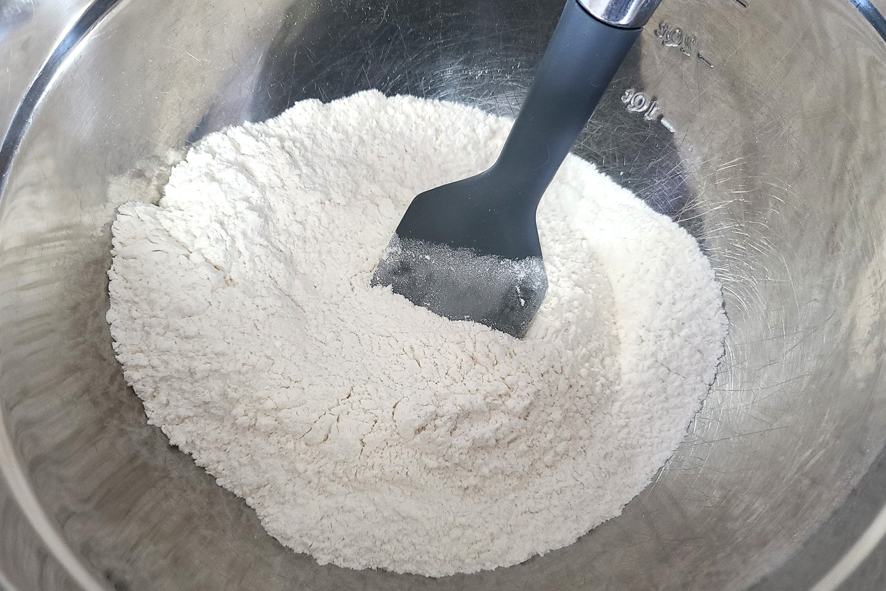 White coloured dry ingredients in a mixing bowl, with a silicone spatula.