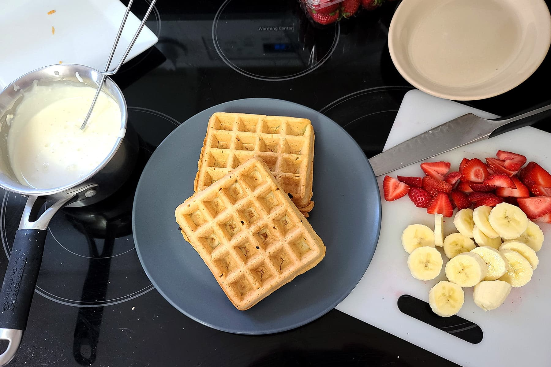 A small saucepan with the cream cheese sauce, a plate with two waffles on it, and the cutting board with sliced strawberries and bananas on it.