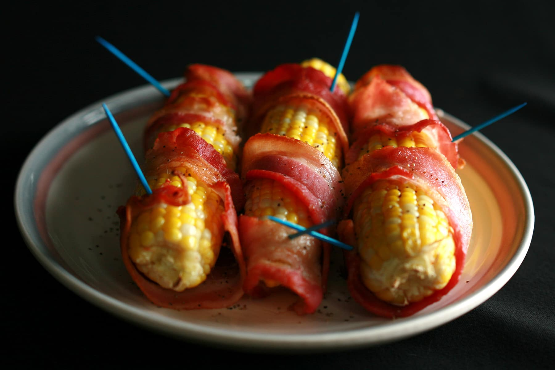 3 cobs of corn wrapped in cooked bacon, on a small plate.