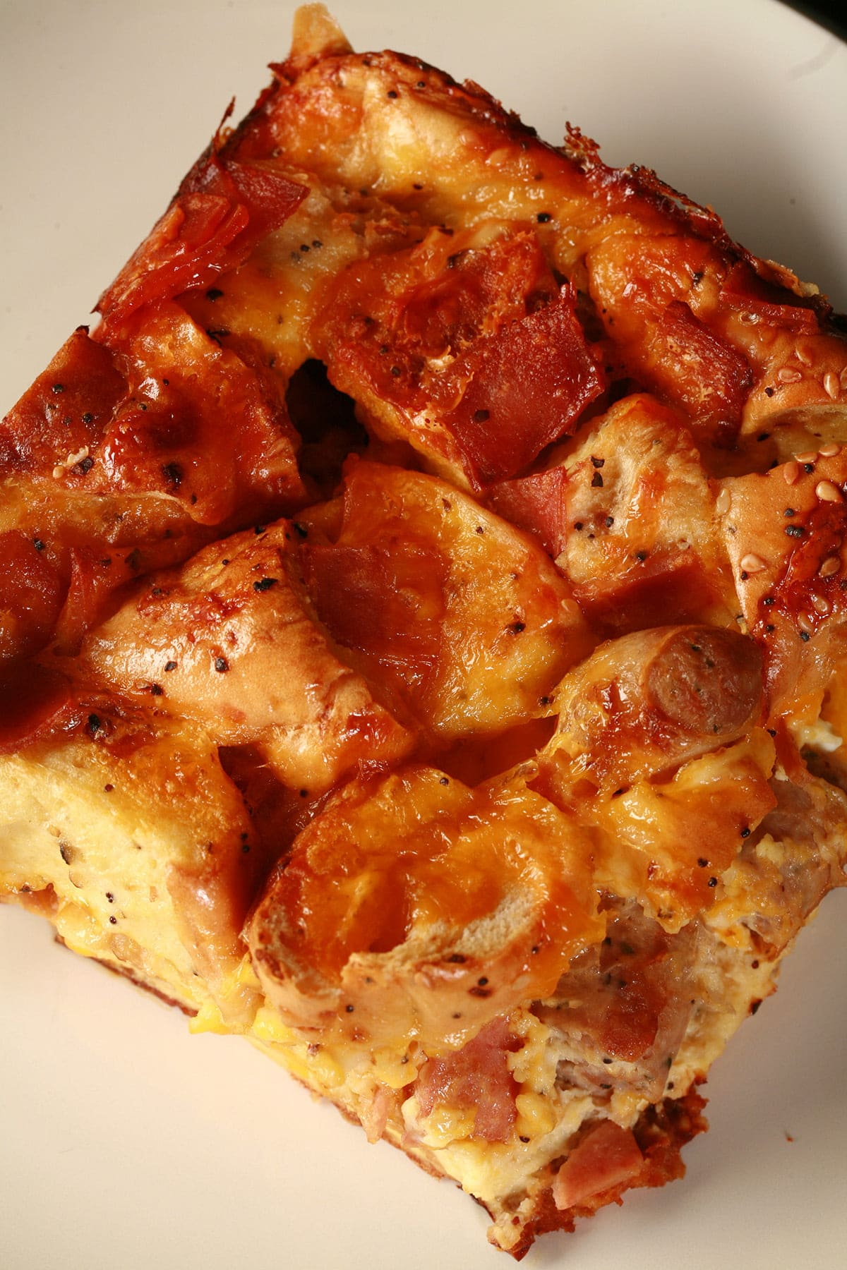 A square serving of breakfast bagel casserole. Eggs, bacon, chunks of bagel, and pieces of sausage are visible in the cheesy casserole.
