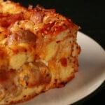 A square serving of breakfast bagel strata. Eggs, bacon, chunks of bagel, and pieces of sausage are visible in the cheesy casserole.