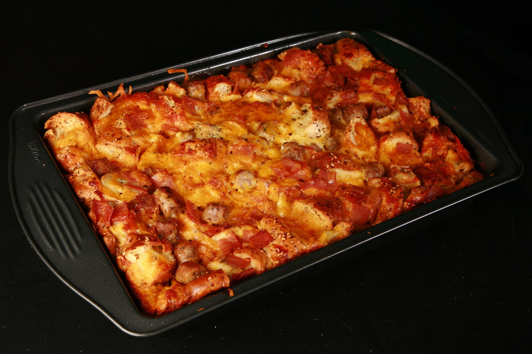 A whole pan of breakfast bagel casserole, fresh out of the oven. It has cooked to a golden brown colour.