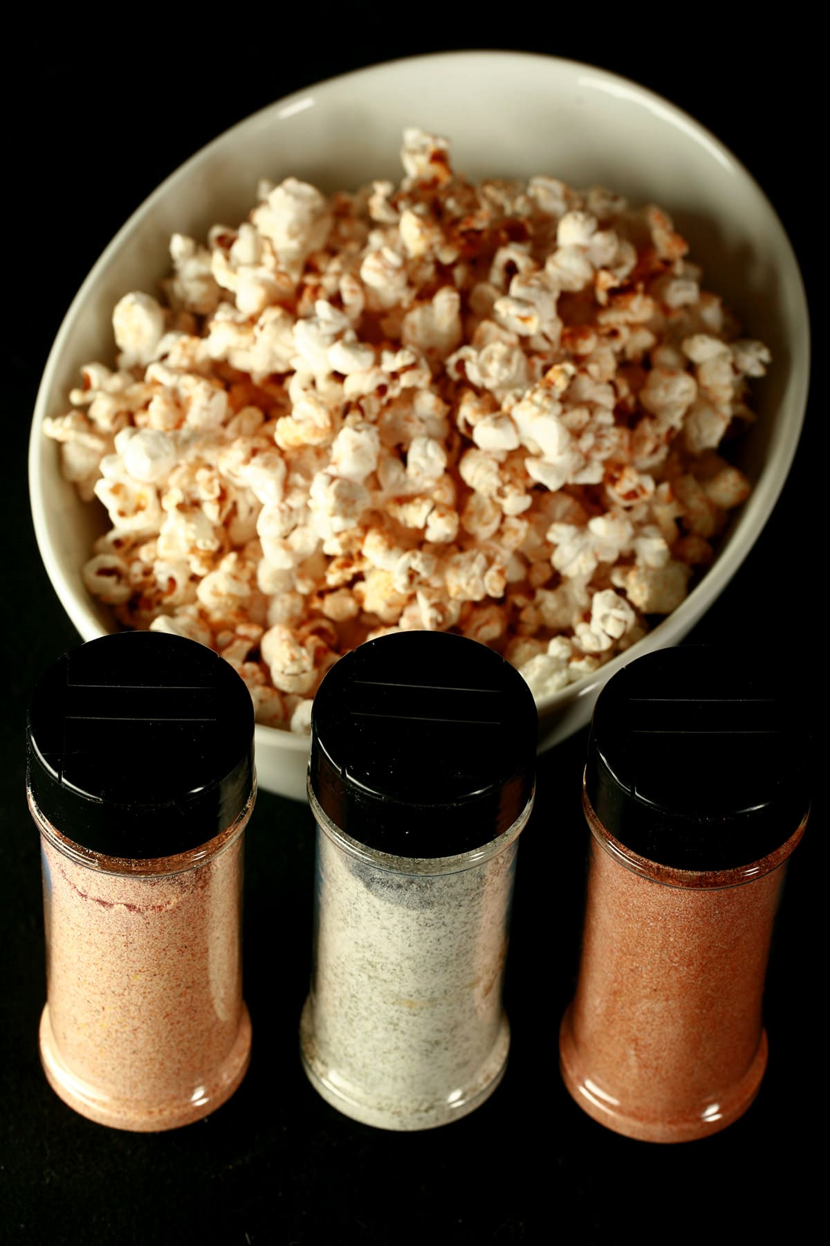 3 small canisters of popcorn seasoning - All Dressed, Dill Pickle, and Ketchup - are lined up in front of a large white bowl of seasoned popcorn.