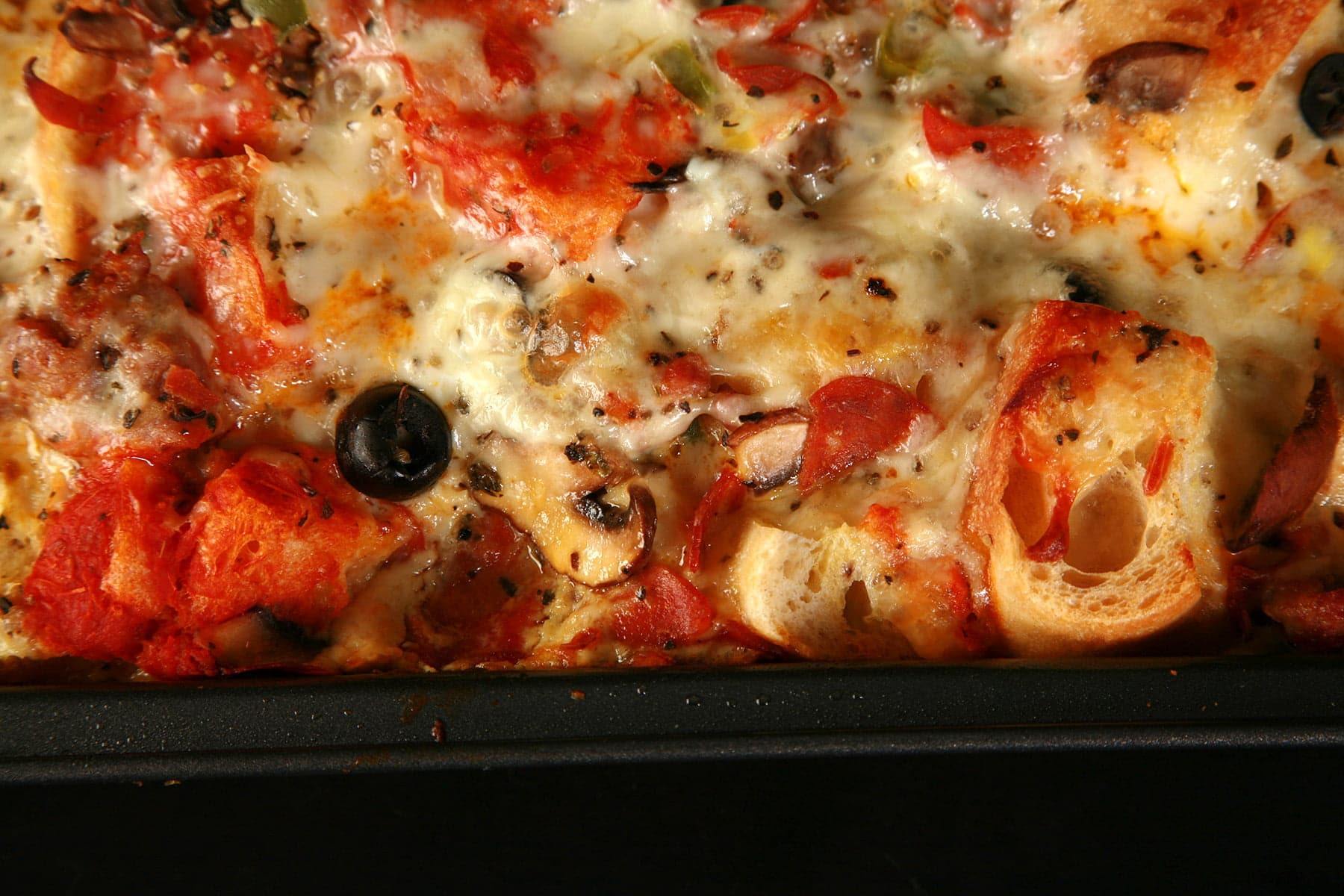 A pan of deluxe pizza bread pudding: A brunch casserole featuring pepperoni, sausage, mushrooms, green peppers, black olives, marinara sauce, and cheese.