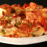 A square of deluxe pizza bread pudding: A brunch casserole featuring pepperoni, sausage, mushrooms, green peppers, black olives, marinara sauce, and cheese.