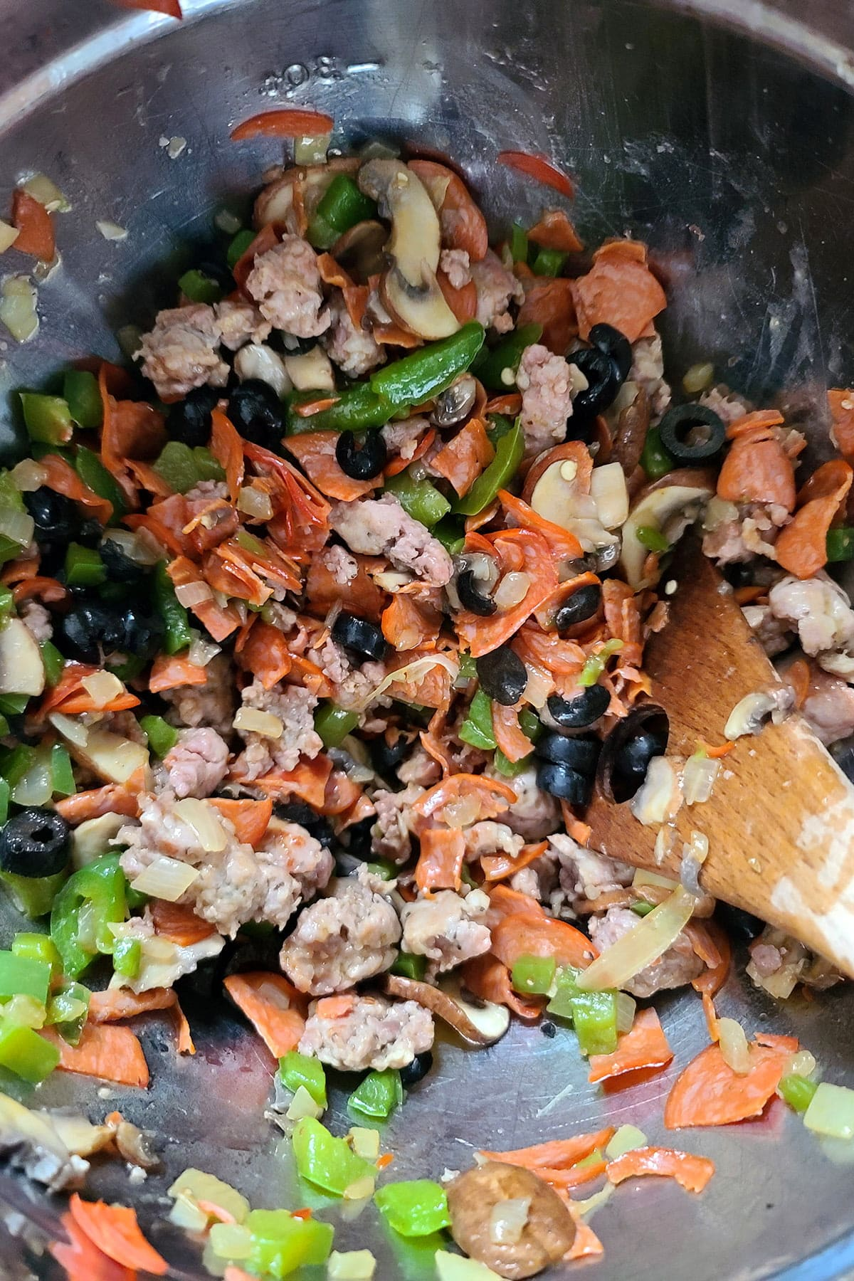 Pepperoni, sausage, green pepper, onion, mushrooms, and black olives together in a bowl.