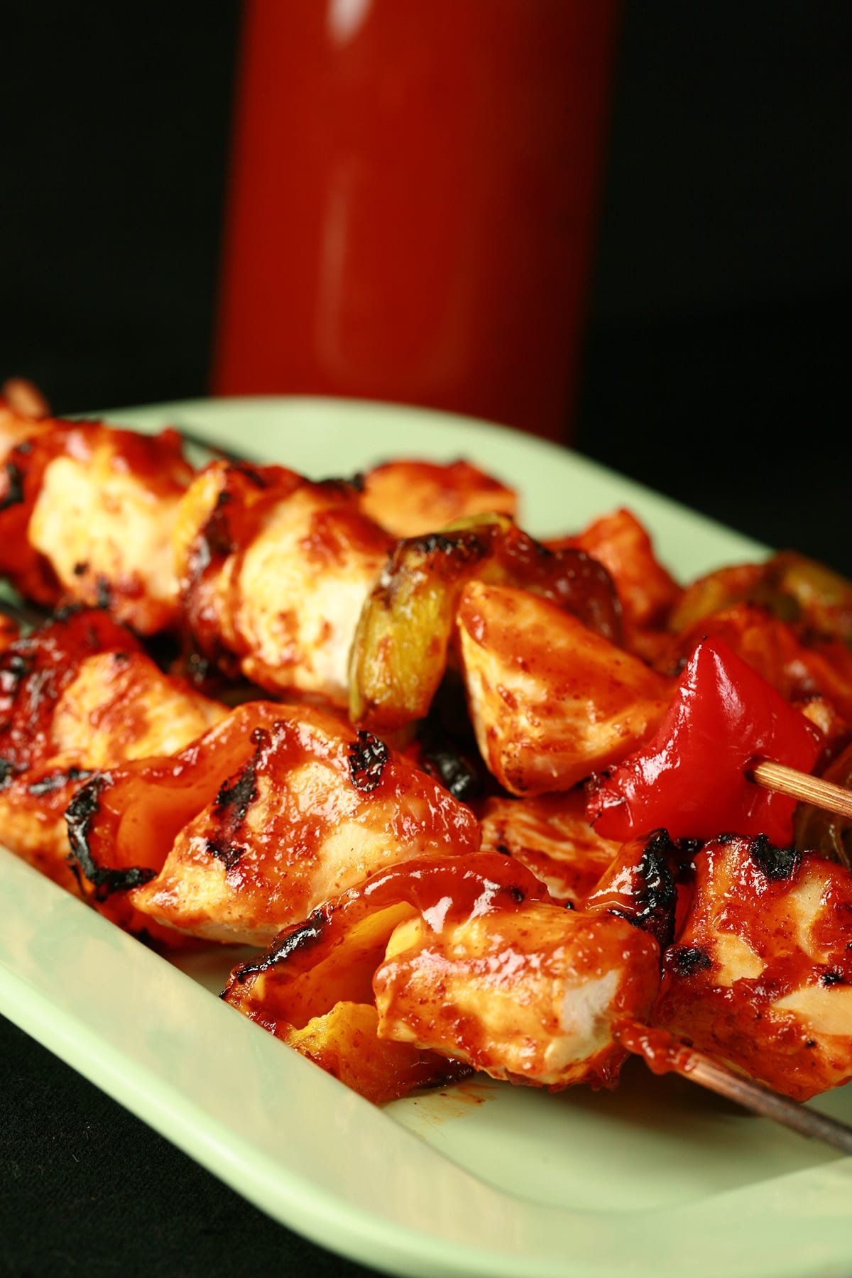 A plate of grilled chicken skewers, with replica Honey Dijon Diana Sauce spread on them. A bottle of the sauce rests behind the plate of food.