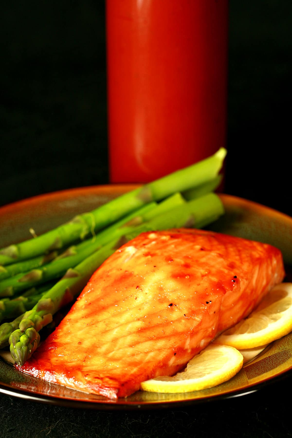 A baked salmon filet, with roasted asparagus. The salmon is coated in replica Diana Maple Sauce. A bottle of the sauce rests behind the plate of food.