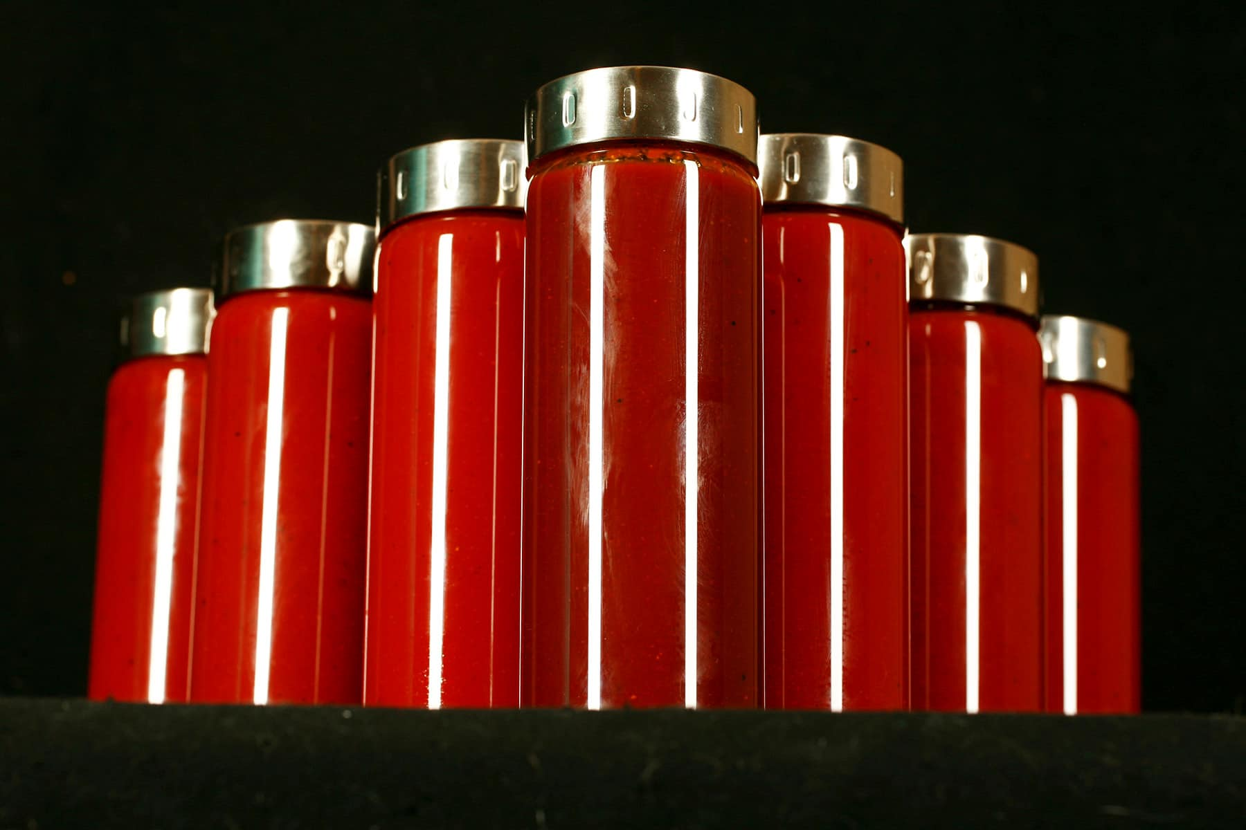 Seven tall, slender glass bottles filled with varying shades of dark red BBQ sauce - Replica Diana Sauce. The jars all have matching stainless lids, and are arranged in a V formation.