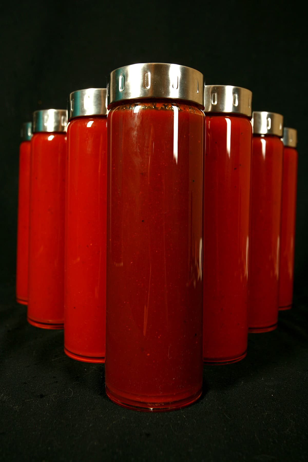 Seven tall, slender glass bottles filled with varying shades of dark red BBQ sauce - Replica Diana BBQ Sauce. The jars all have matching stainless lids, and are arranged in a V formation.