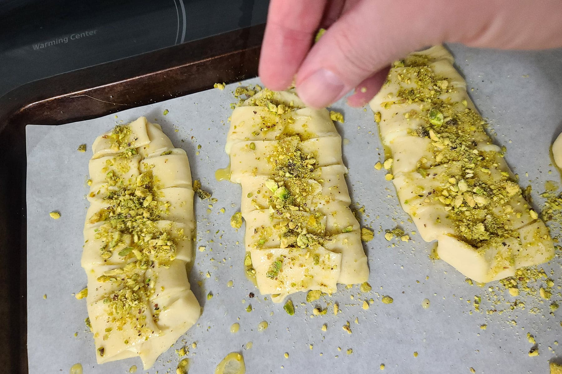 A hand sprinkles chopped pistachios over each pastry.