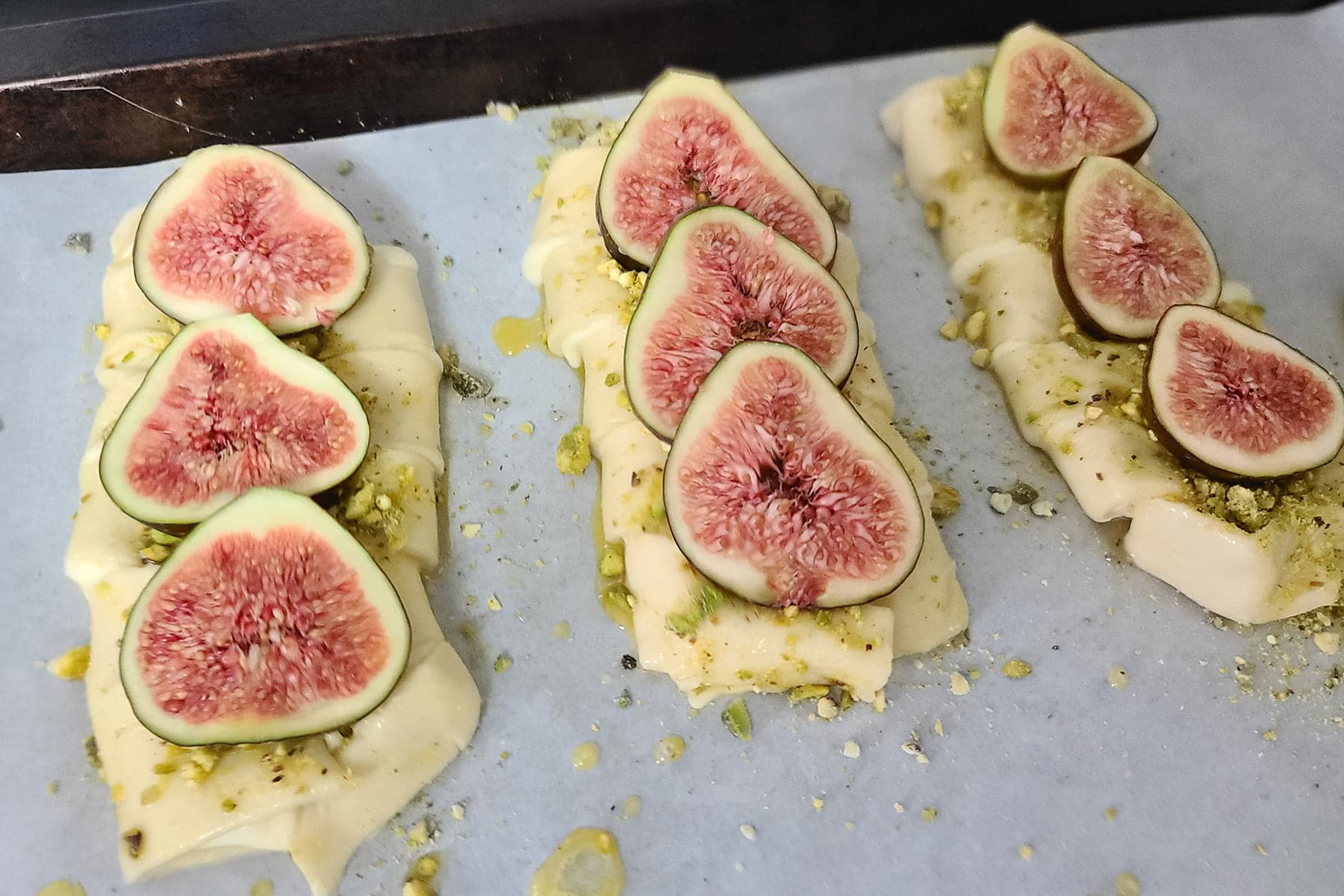 3 braided pastries are shown, each with a line of sliced figs arranged up the center.