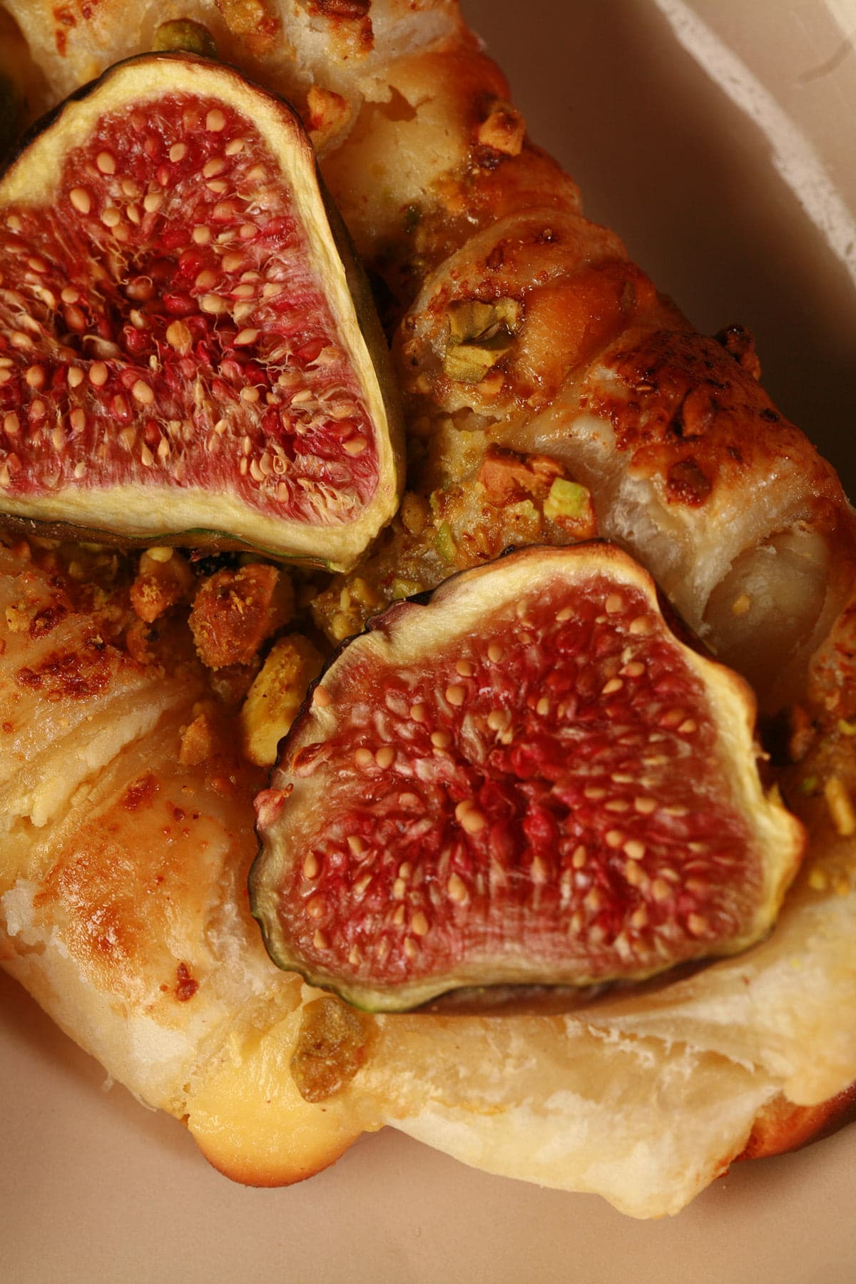 A close up view of two fig, honey, and goat cheese strudel pastries on a tan coloured plate.