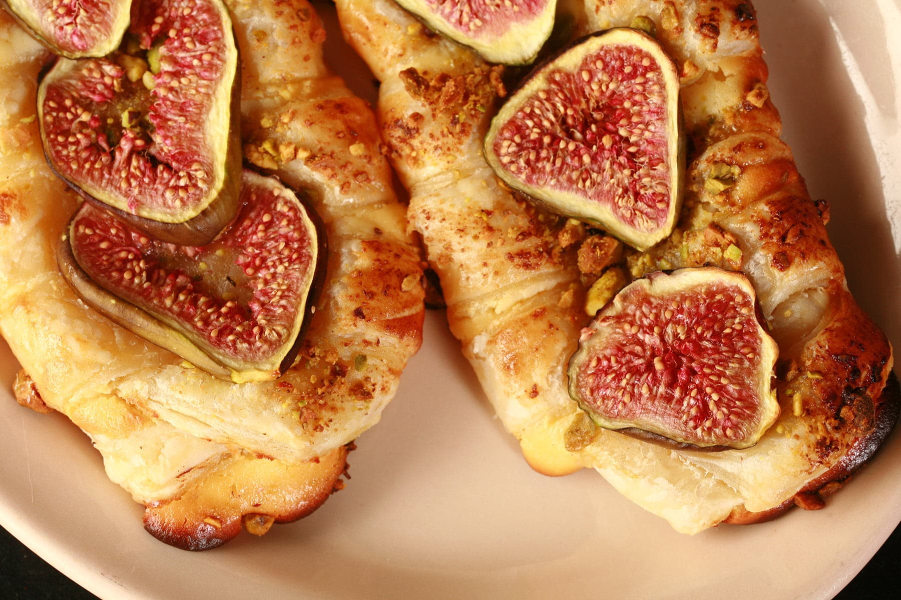 A close up view of two fig, honey, and goat cheese strudels on a tan coloured plate.