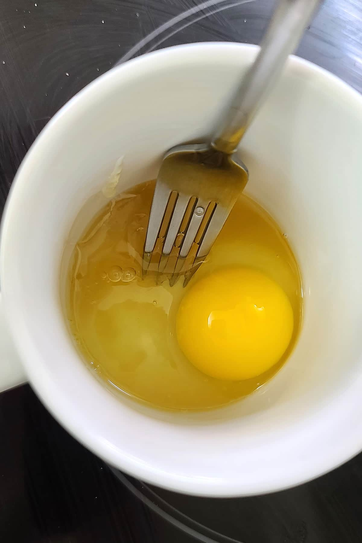 An egg and some honey in a mug, about to be whisked together.