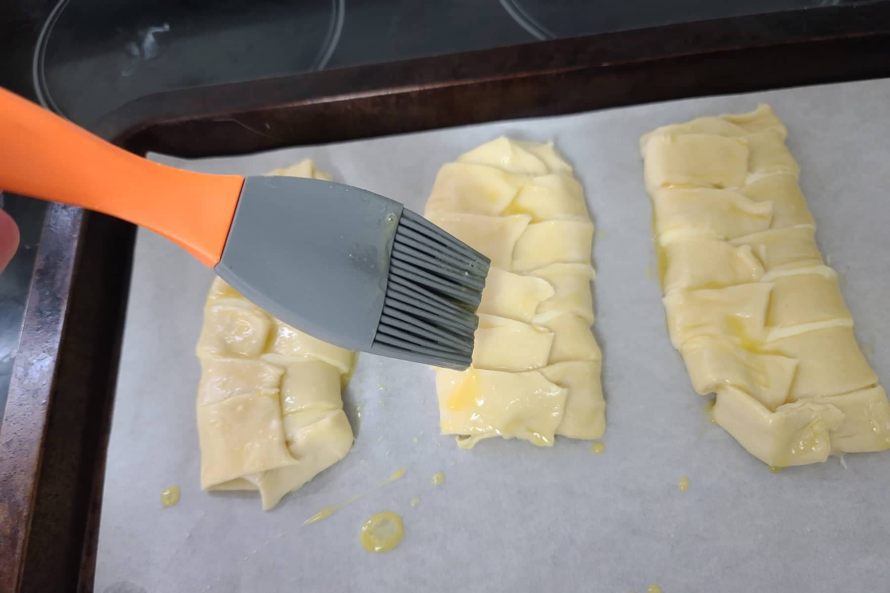 A silicone pastry brush is used to brush honey-egg mixture over the braided pastries.