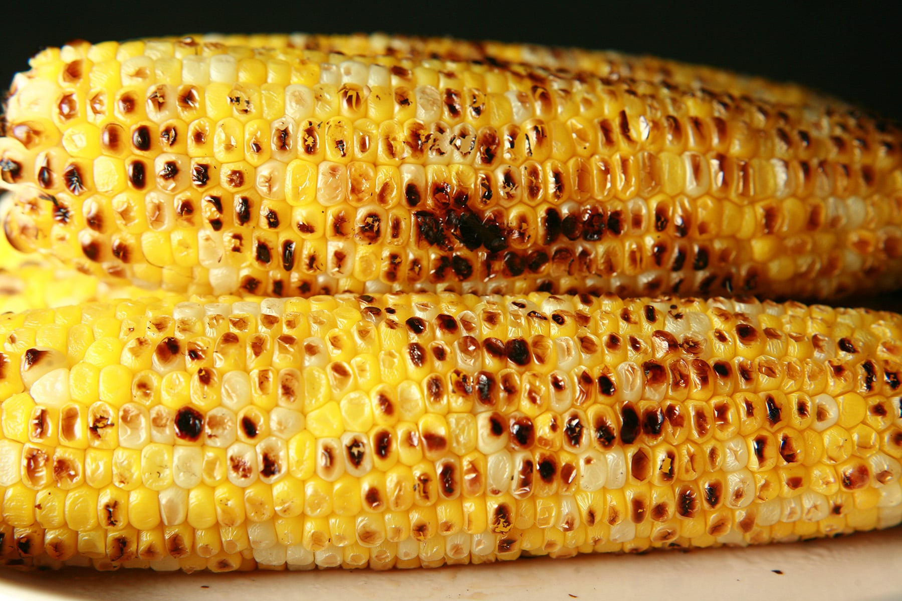 A pile of 5 ears of grilled corn on the cob, on a beige plate.